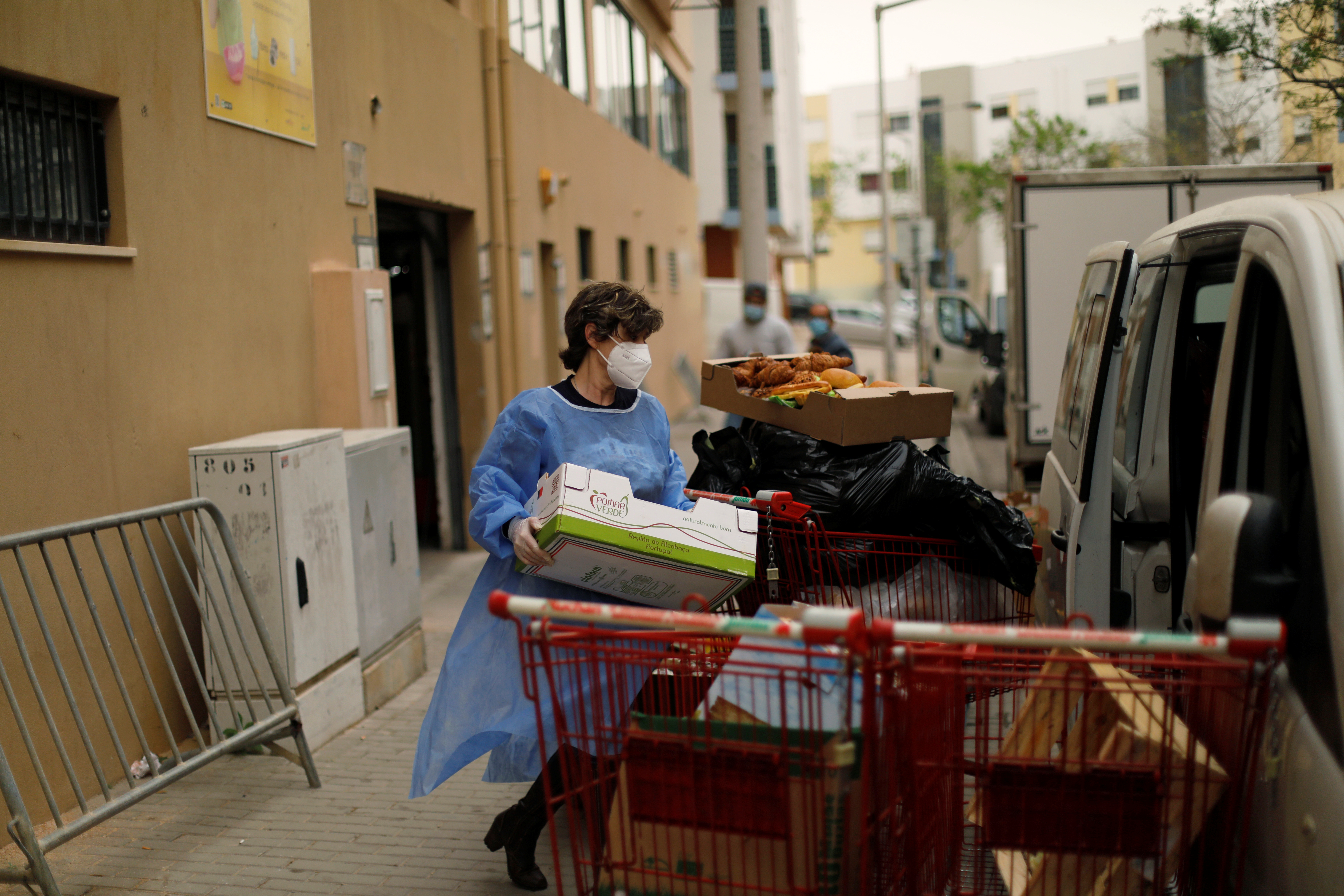 A woman carries goods collected on the Faro Food Bank Against Hunger to a truck, during the coronavirus disease (COVID-19) pandemic in Faro, Portugal, March 30, 2021. Picture taken March 30, 2021. REUTERS/Pedro Nunes