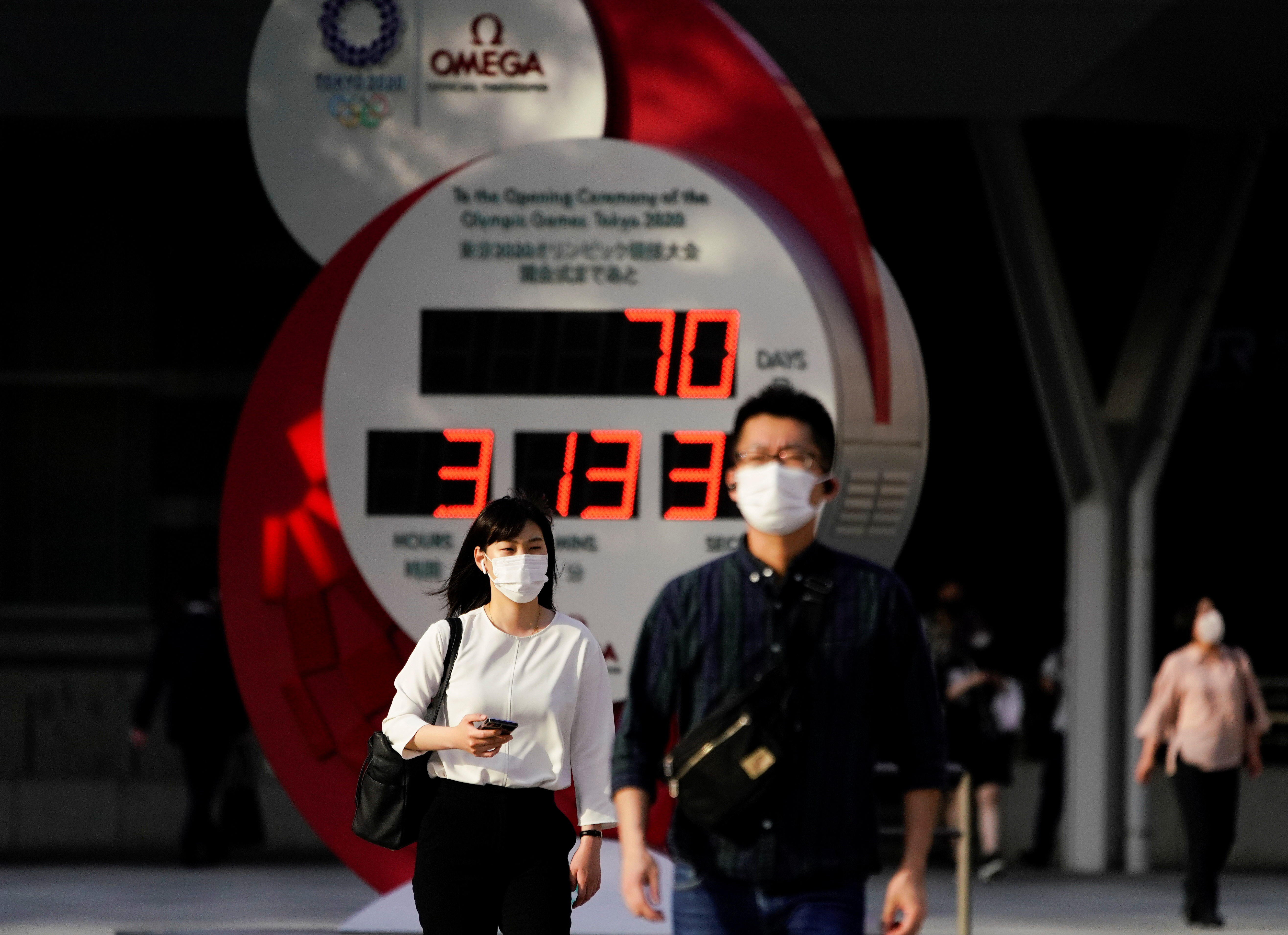 Passersby wearing protective face masks walk near a countdown clock of Tokyo 2020 Olympic Games that have been postponed to 2021 due to the coronavirus disease (COVID-19) outbreak, in Tokyo, Japan May 14, 2021.  REUTERS/Naoki Ogura