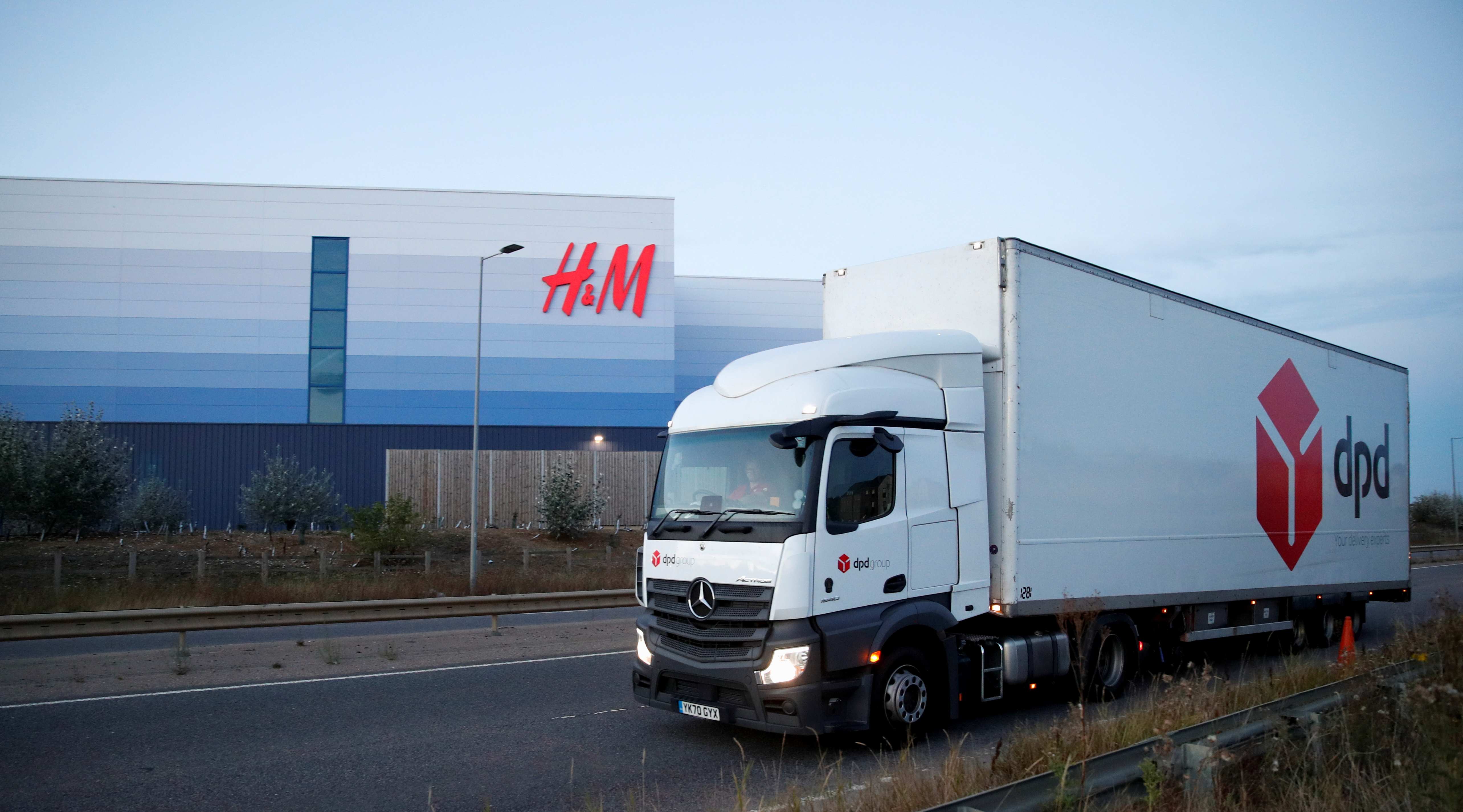 A DPD lorry drives past an H&M warehouse at Magna Park in Milton Keynes, Britain, September 26, 2021.  REUTERS/Andrew Boyers