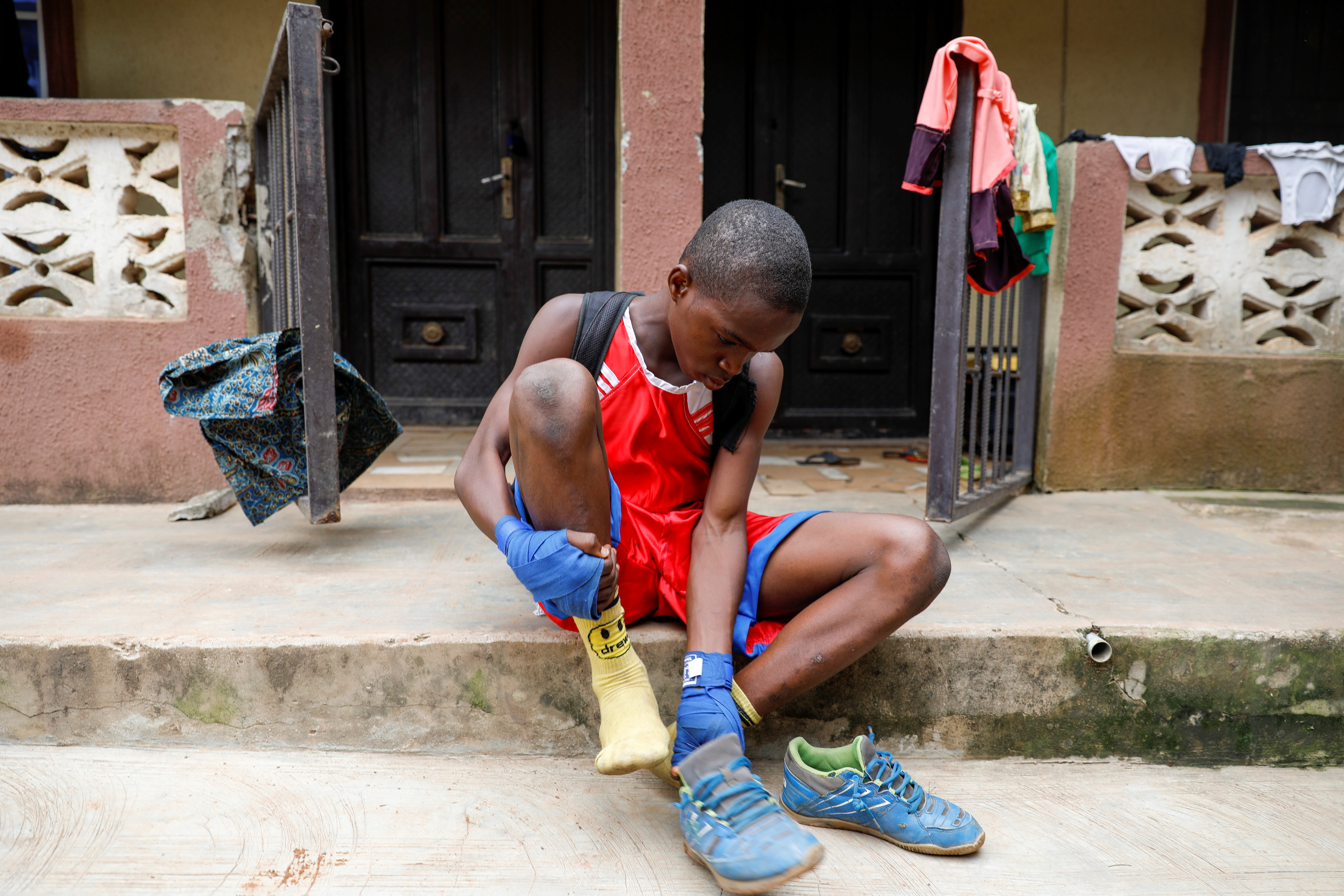 Boxer Tijani Abdulazeez, popularly known as TJ, 15, removes his shoes as he gets home after a training session in Lagos, Nigeria June 5, 2021. REUTERS/Temilade Adelaja
