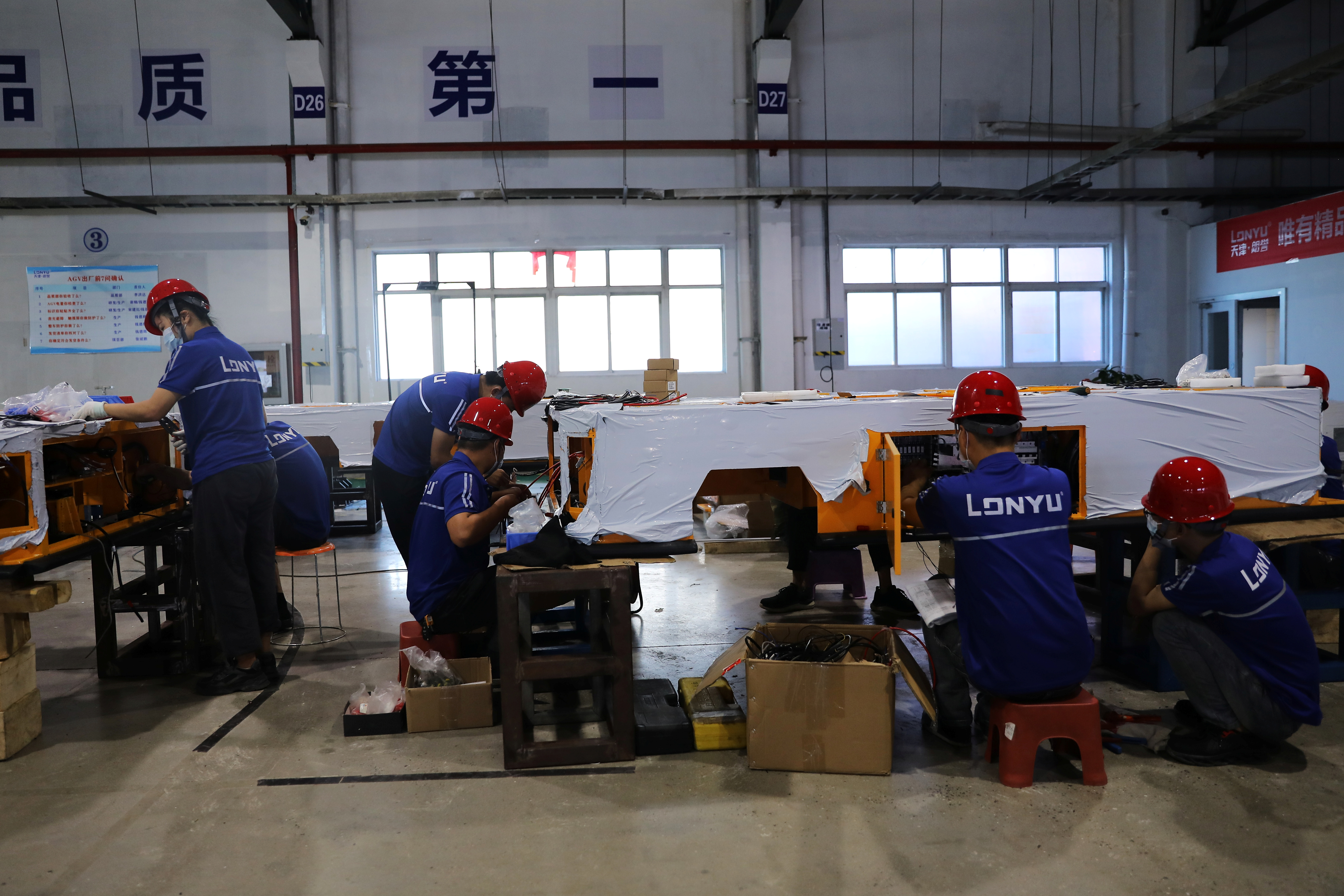 Employees work on assembling automated guided vehicles (AGV) at a Lonyu Robot Co factory in Tianjin, China, September 7, 2021. REUTERS/Tingshu Wang