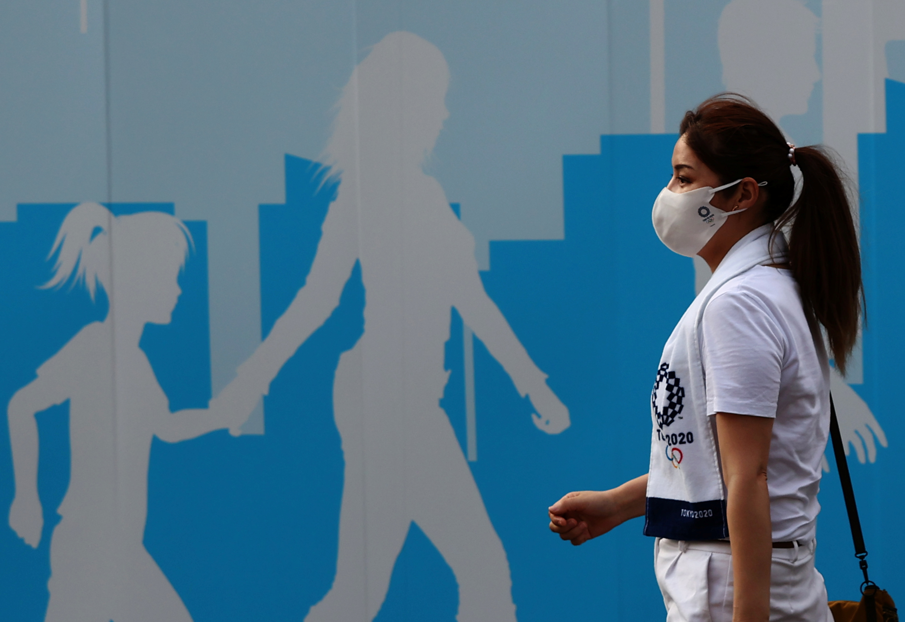 A woman wearing a protective mask, amid the coronavirus disease (COVID-19) outbreak, walks past a fence outside the National Stadium, the main venue of the Tokyo 2020 Olympic Games in Tokyo, Japan, July 28, 2021.   REUTERS/Kim Kyung-Hoon