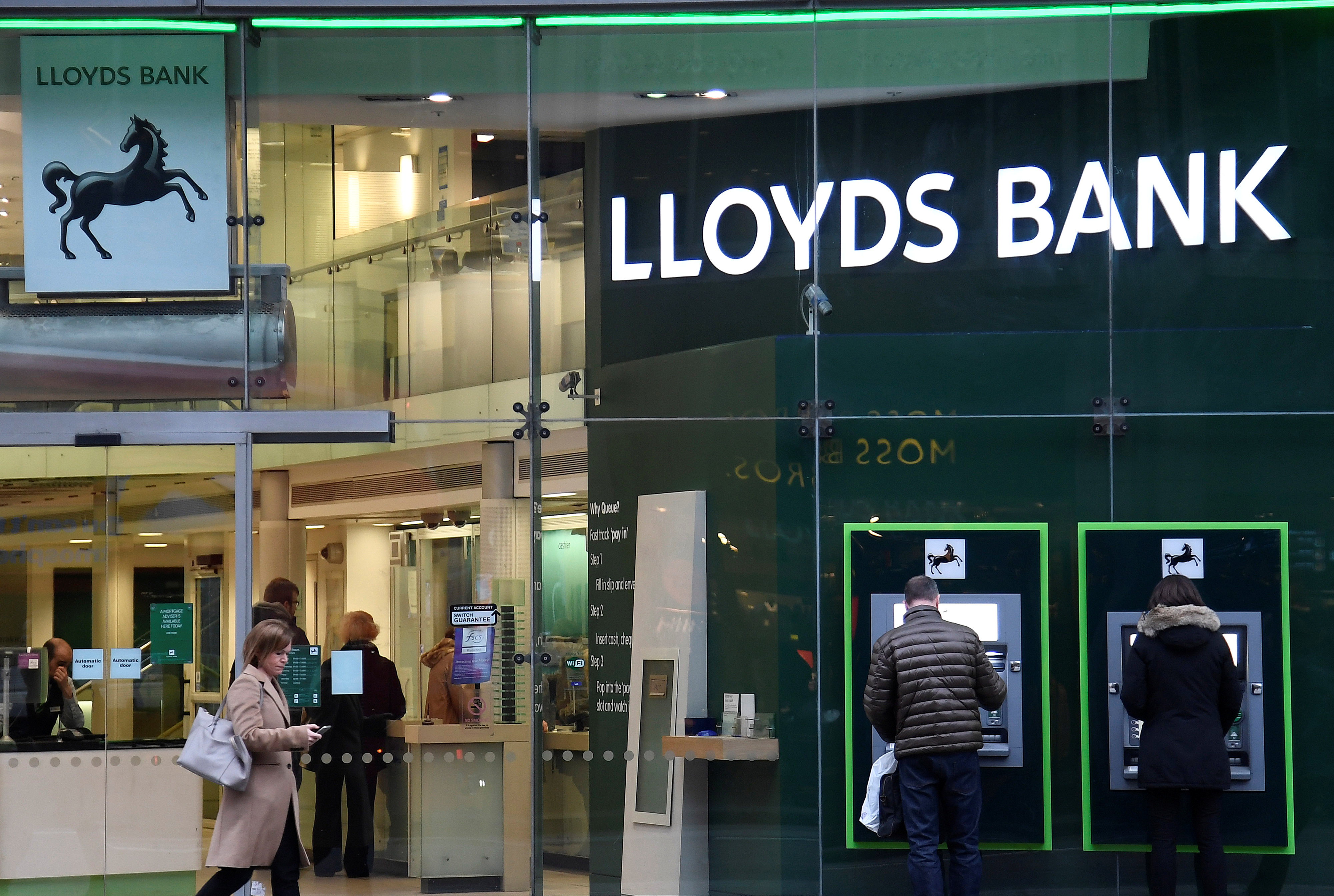 Customers use ATMs at a branch of Lloyds Bank in London, Britain, February 21, 2017. REUTERS/Toby Melville/File Photo