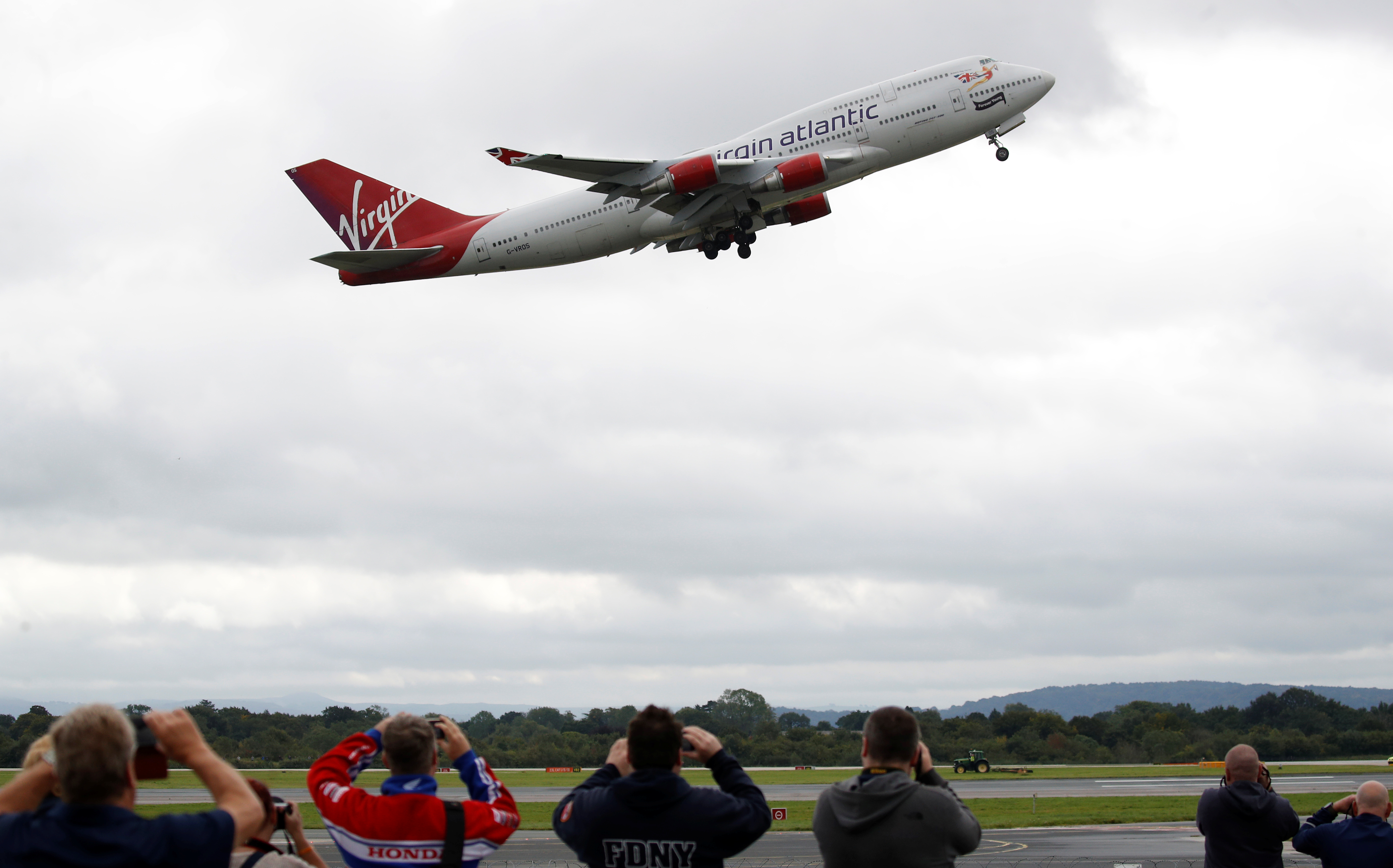 Aviation enthusiasts gather at the aviation viewing park to watch Virgin Atlantic's penultimate Boeing 747-400 aircraft 'Forever Young' depart for the final time before being retired from the fleet at Manchester Airport, Britain, September 8, 2020. REUTERS/Phil Noble