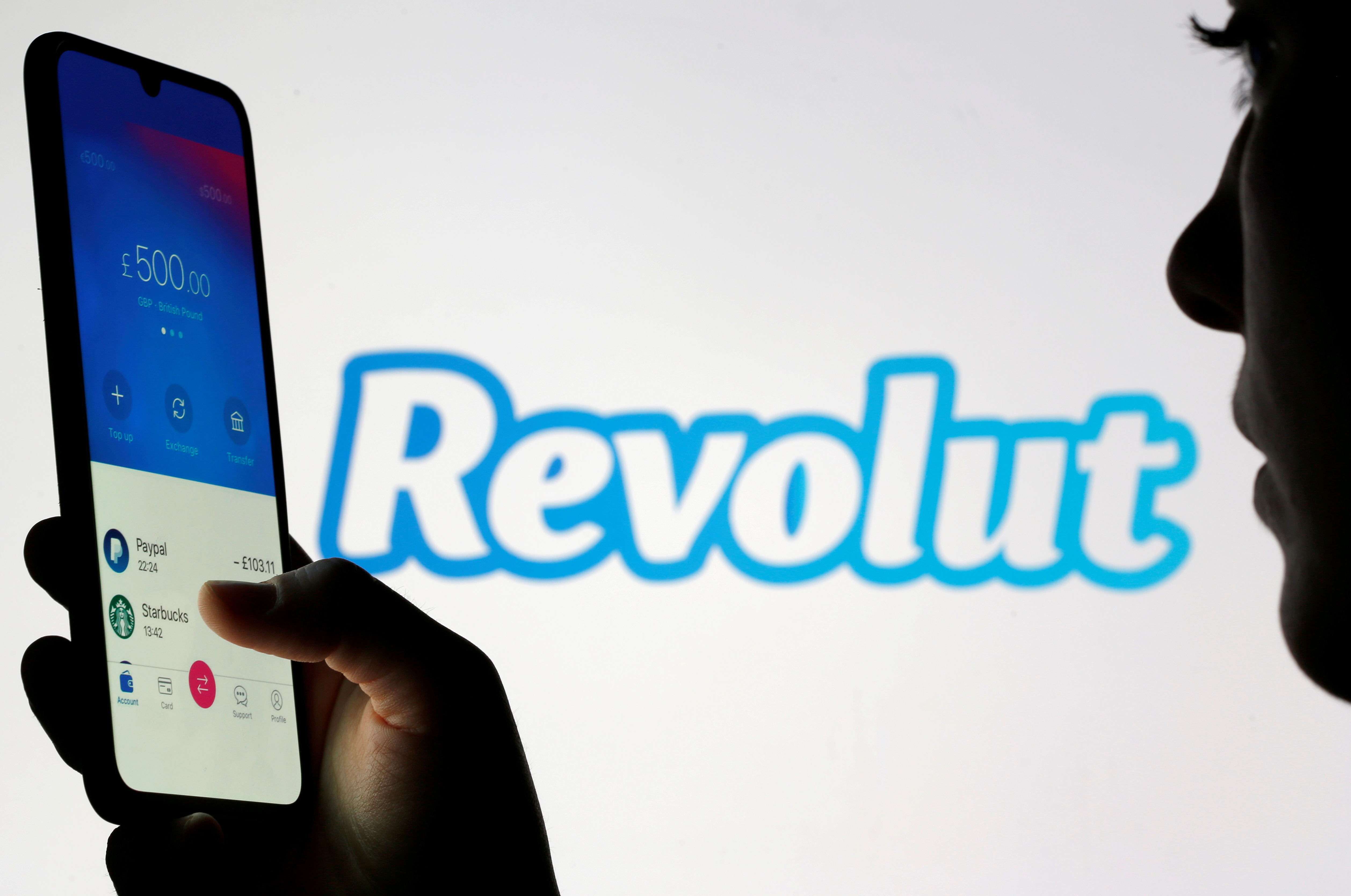 Woman holds smartphone with the Revolut app in front of a displayed Revolut logo in this illustration taken February 4, 2020. REUTERS/Dado Ruvic/Illustration