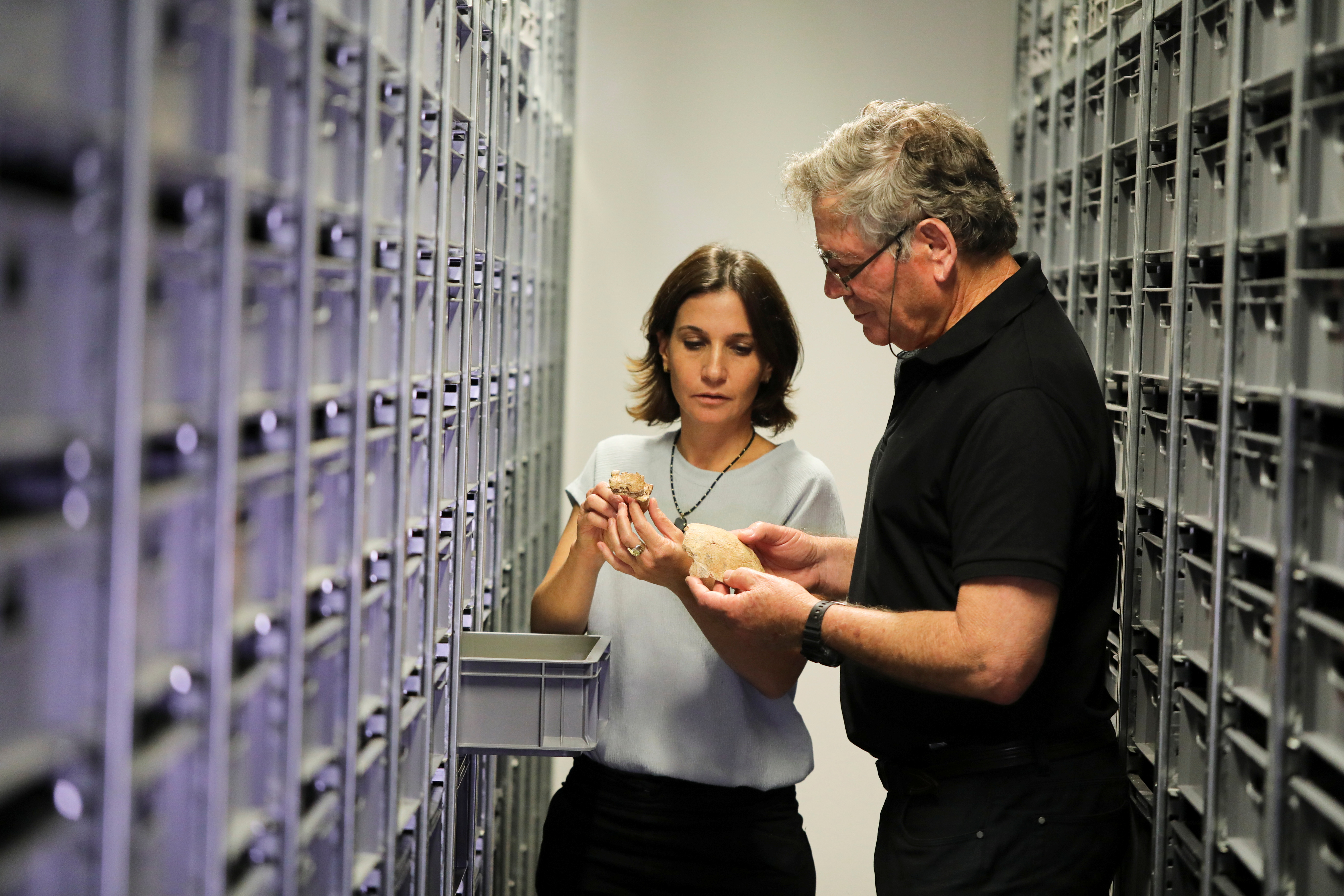 Tel Aviv University Professor Israel Hershkovitz and Doctor Hila May from Tel Aviv University, hold what scientists say are two pieces of fossilised bone of a previously unknown kind of early human discovered at the Nesher Ramla site in central Israel, during an interview with Reuters at The Steinhardt Museum of Natural History in Tel Aviv, Israel June 23, 2021. Picture taken June 23, 2021. REUTERS/Ammar Awad