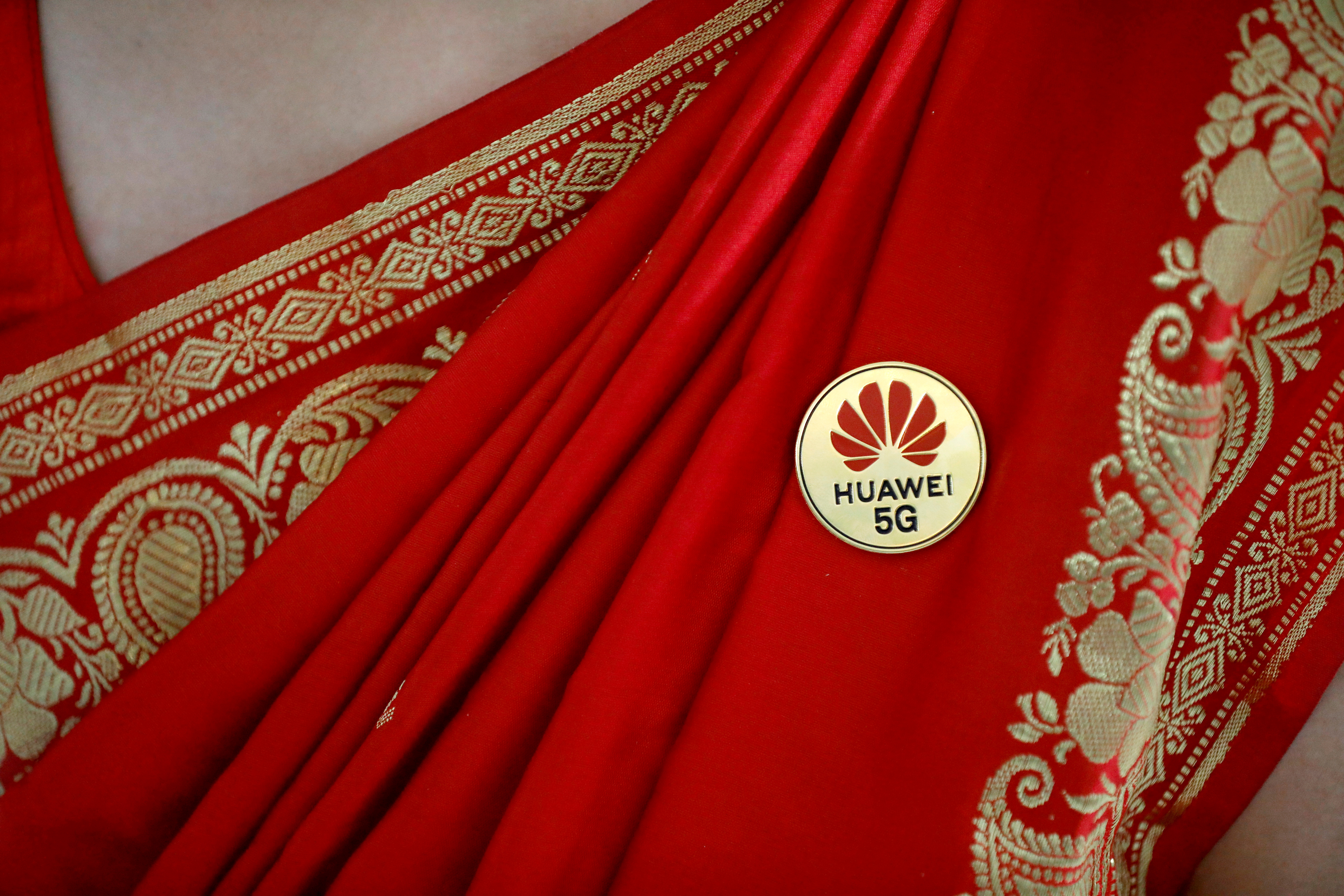 Huawei's logo is seen on a badge pinned on a saree of a lady at the India Mobile Congress in New Delhi, India, October 14, 2019. REUTERS/Anushree Fadnavis
