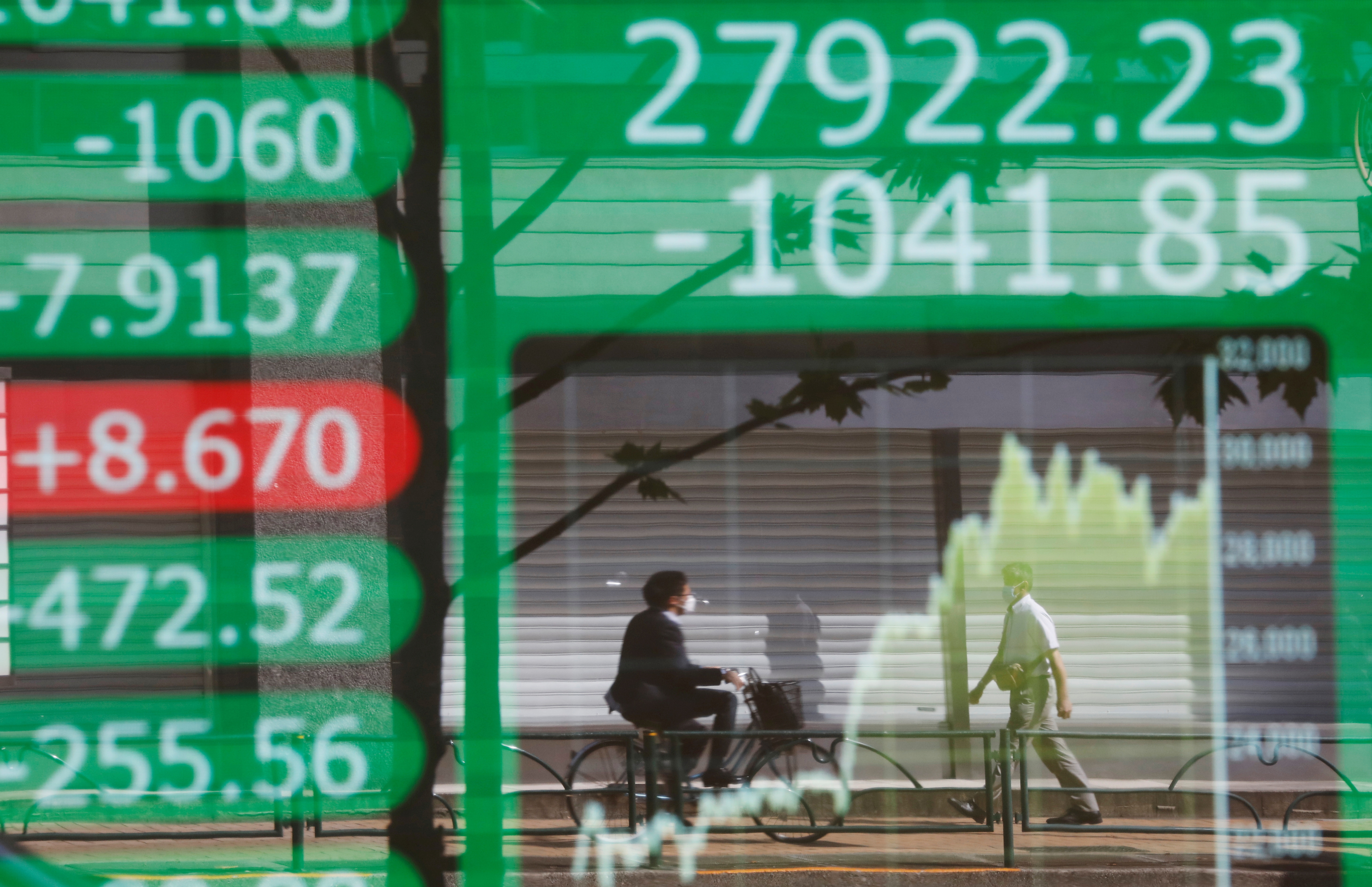People are reflected on an electric board showing Nikkei index and its graph outside a brokerage at a business district in Tokyo, Japan, June 21, 2021.   REUTERS/Kim Kyung-Hoon/File Photo
