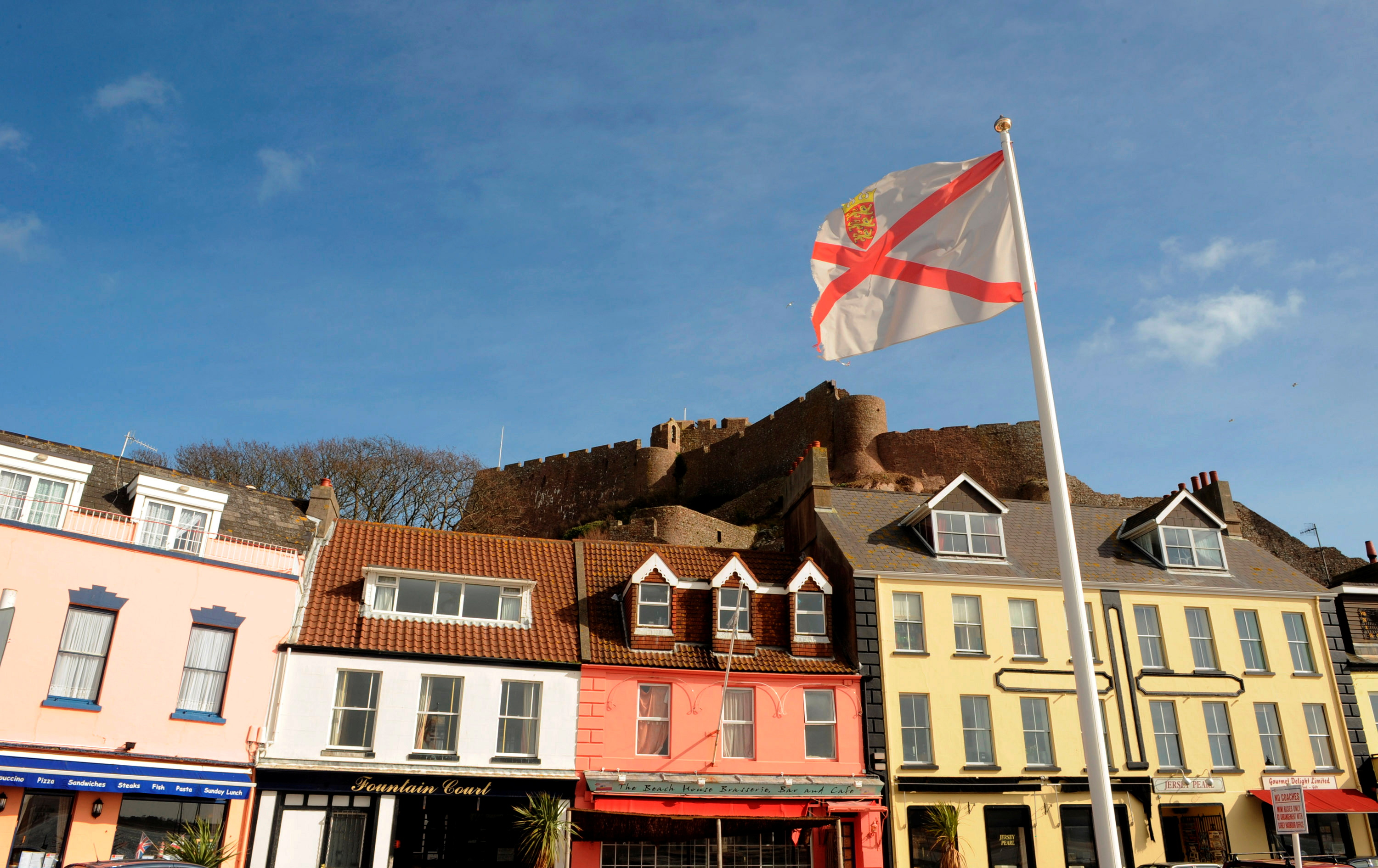 The Mont Orgueil Castle is seen behind an island flag at Gorey Harbour in Jersey, in this February 26, 2008 file photo.  REUTERS/Toby Melville
