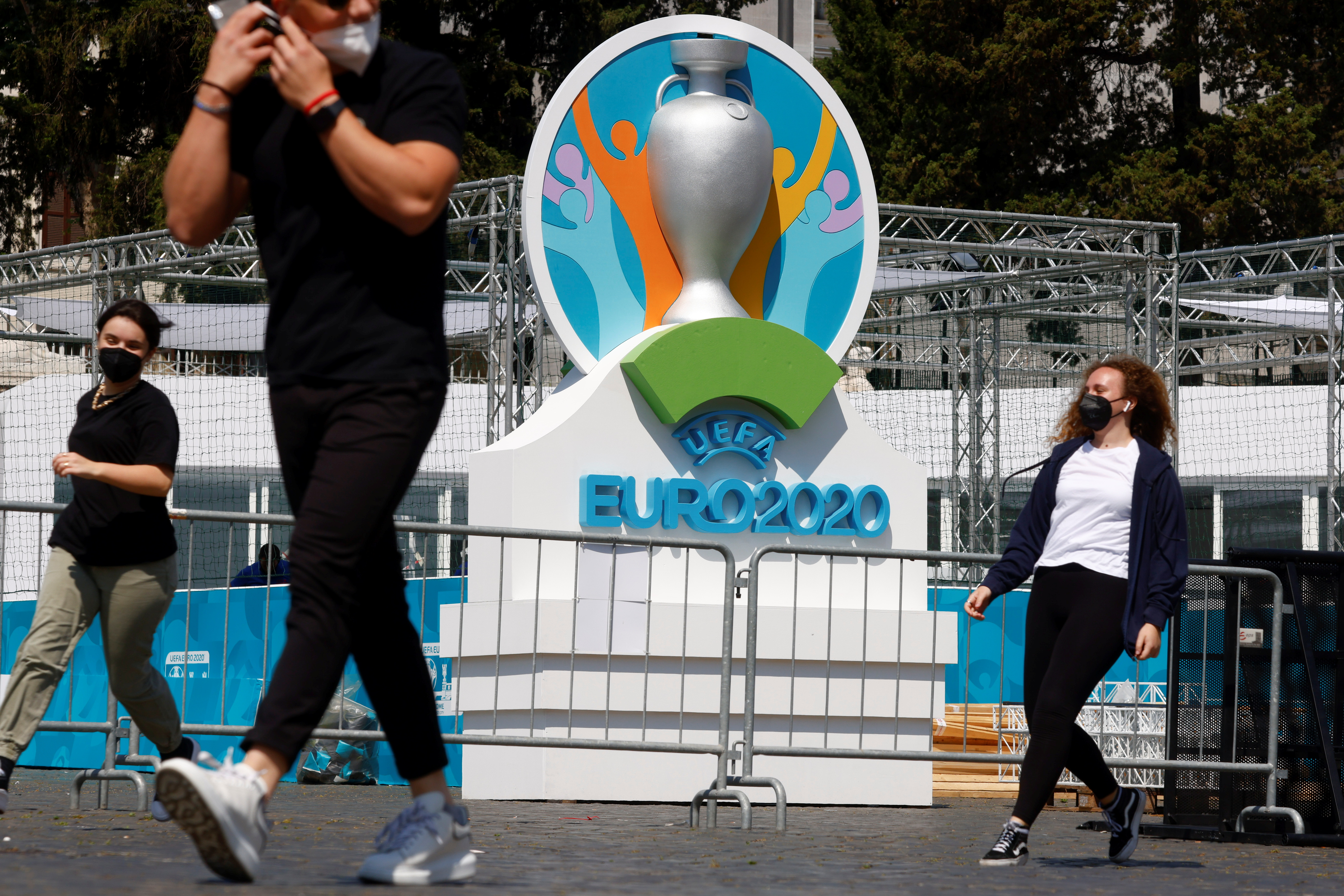 People wearing protective masks walk past the logo of UEFA Euro 2020 at the fan zone at Piazza del Popolo in Rome, Italy, June 7, 2021. REUTERS/Guglielmo Mangiapane