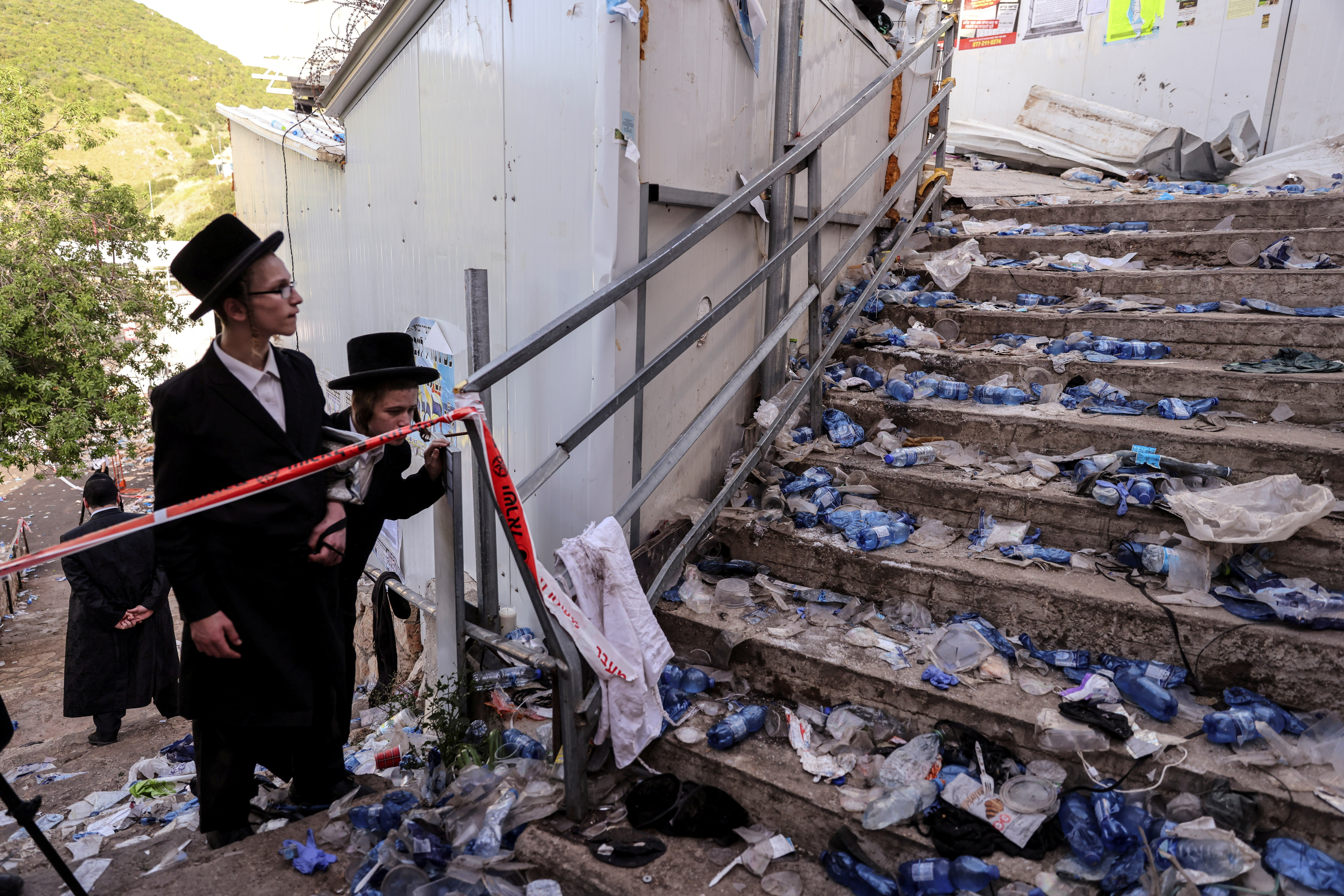 Ultra Orthodox Jews look at stairs with waste on it in Mount Meron, northern Israel, where fatalities were reported among the thousands of ultra-Orthodox Jews gathered at the tomb of a 2nd-century sage for annual commemorations that include all-night prayer and dance, April 30, 2021. REUTERS/ Ronen Zvulun