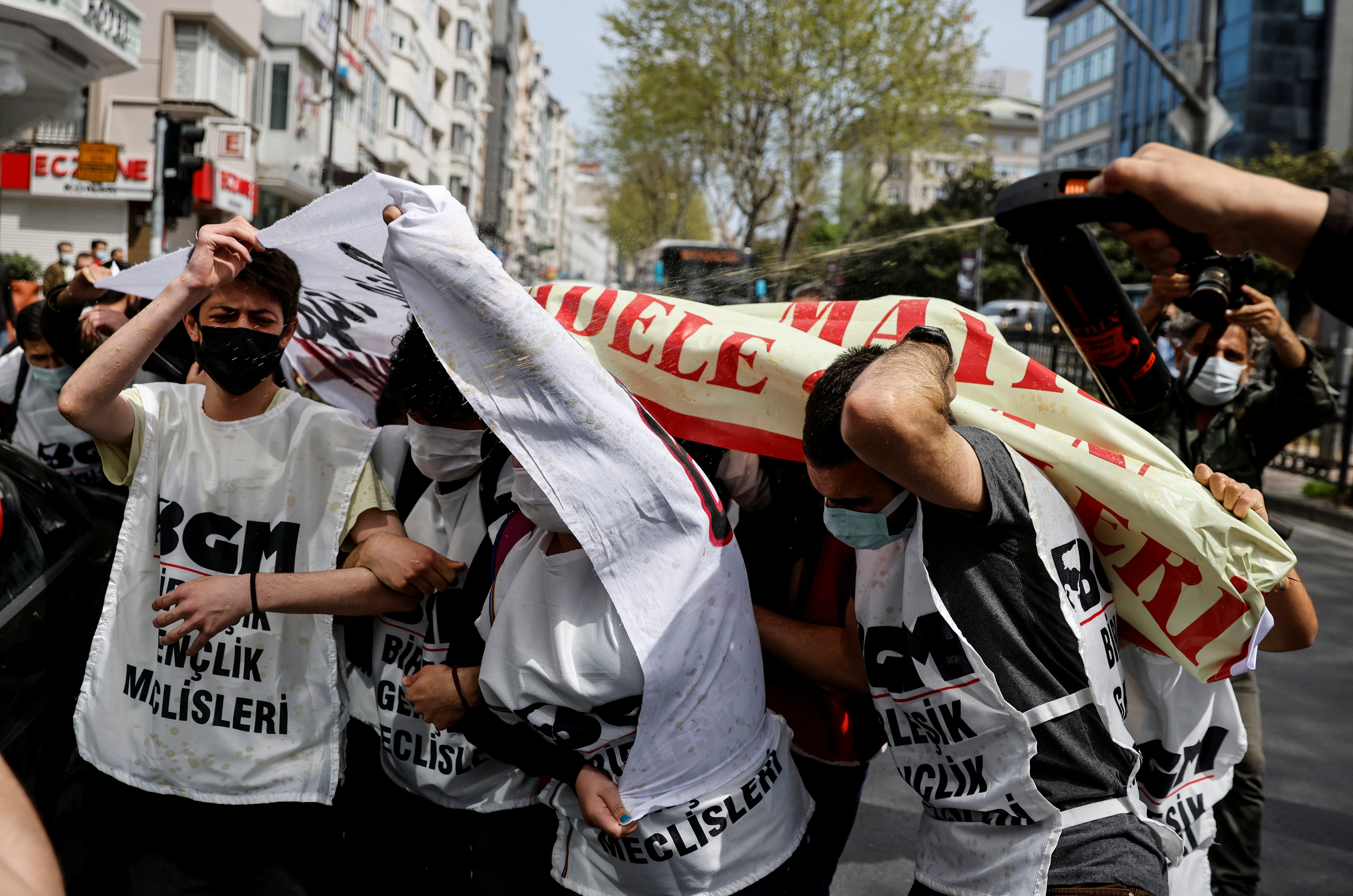 """A police officer uses pepper spray against demonstrators as they attempt to defy a ban and march on Taksim Square to celebrate May Day, during a nationwide """"full closure"""" imposed to slow the rate of the coronavirus disease (COVID-19) contagion, in Istanbul, Turkey May 1, 2021. REUTERS/Umit Bektas"""