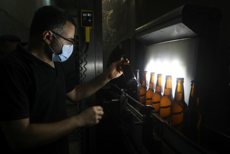 A worker holds a bottle of beer inside a beer factory in Mazraat Yachouh, Lebanon June 11, 2021.  REUTERS/Mohamed Azakir