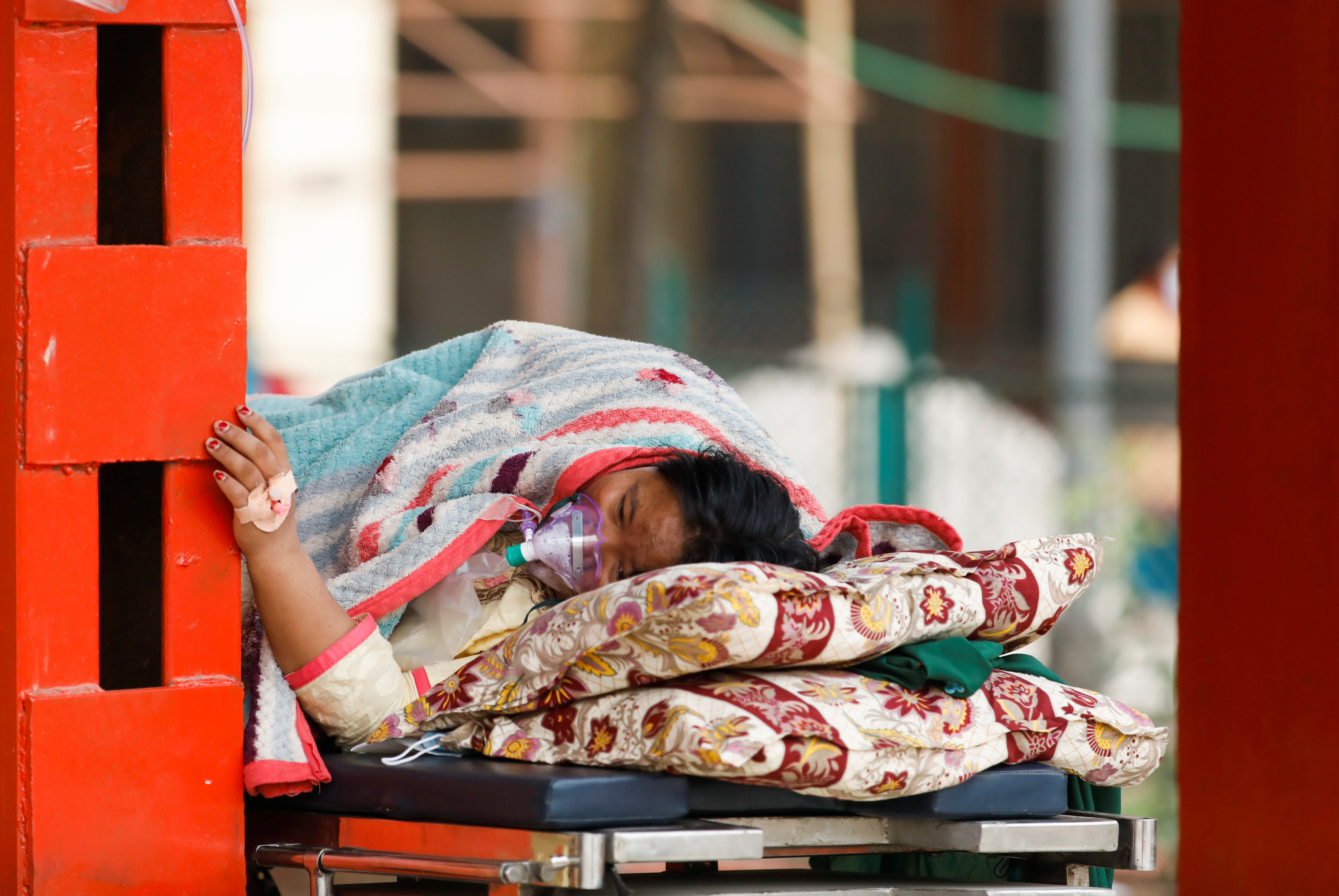 A patient receives oxygen as she waits outside the passage of a hospital due to a lack of free beds inside the hospital for coronavirus disease (COVID-19) patients, as the second major coronavirus wave surges in Kathmandu, Nepal, May 10, 2021. REUTERS/Navesh Chitrakar