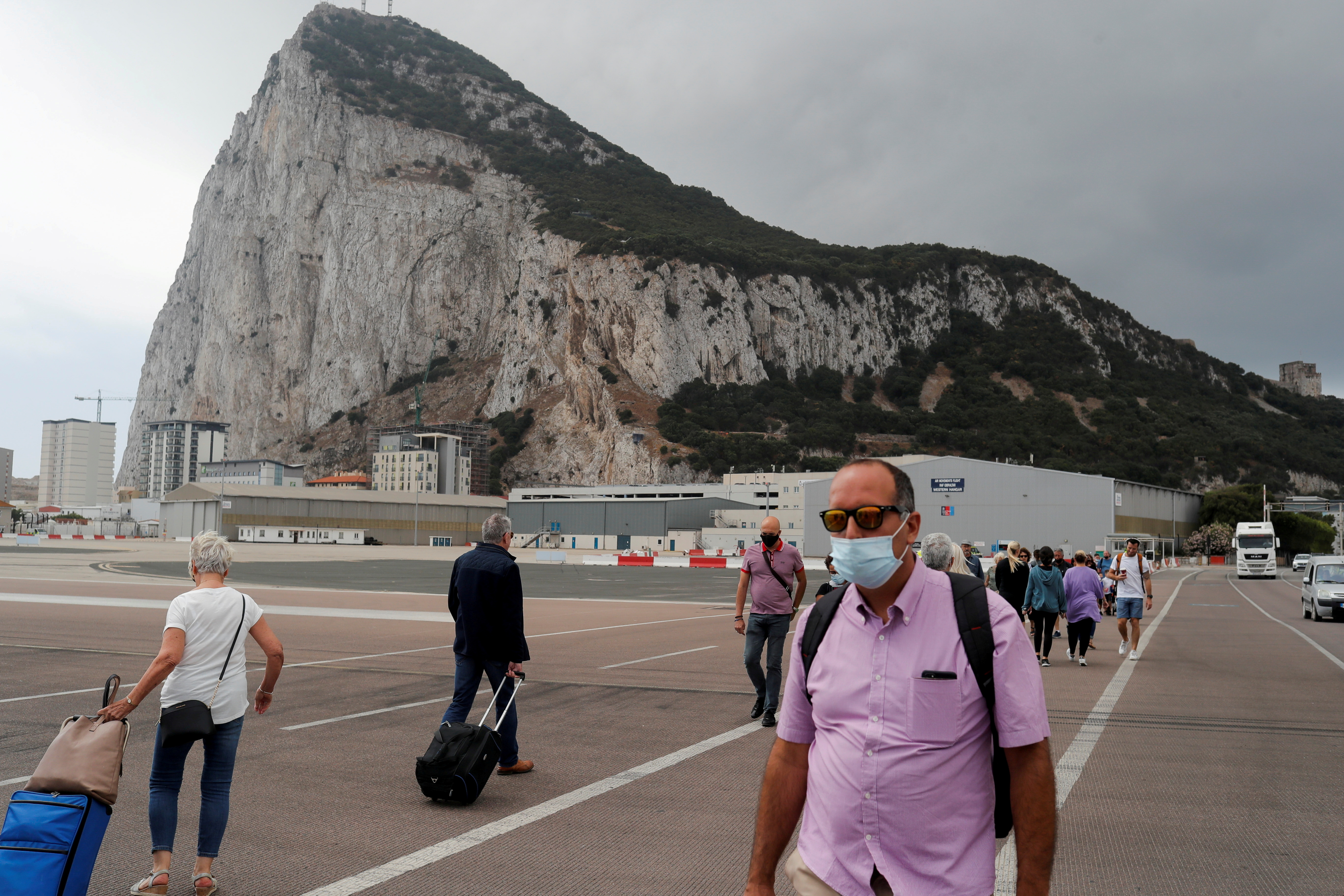 People cross the tarmac of the airport in front of the Rock of Gibraltar in the British overseas territory of Gibraltar, June 24, 2021. REUTERS/Jon Nazca