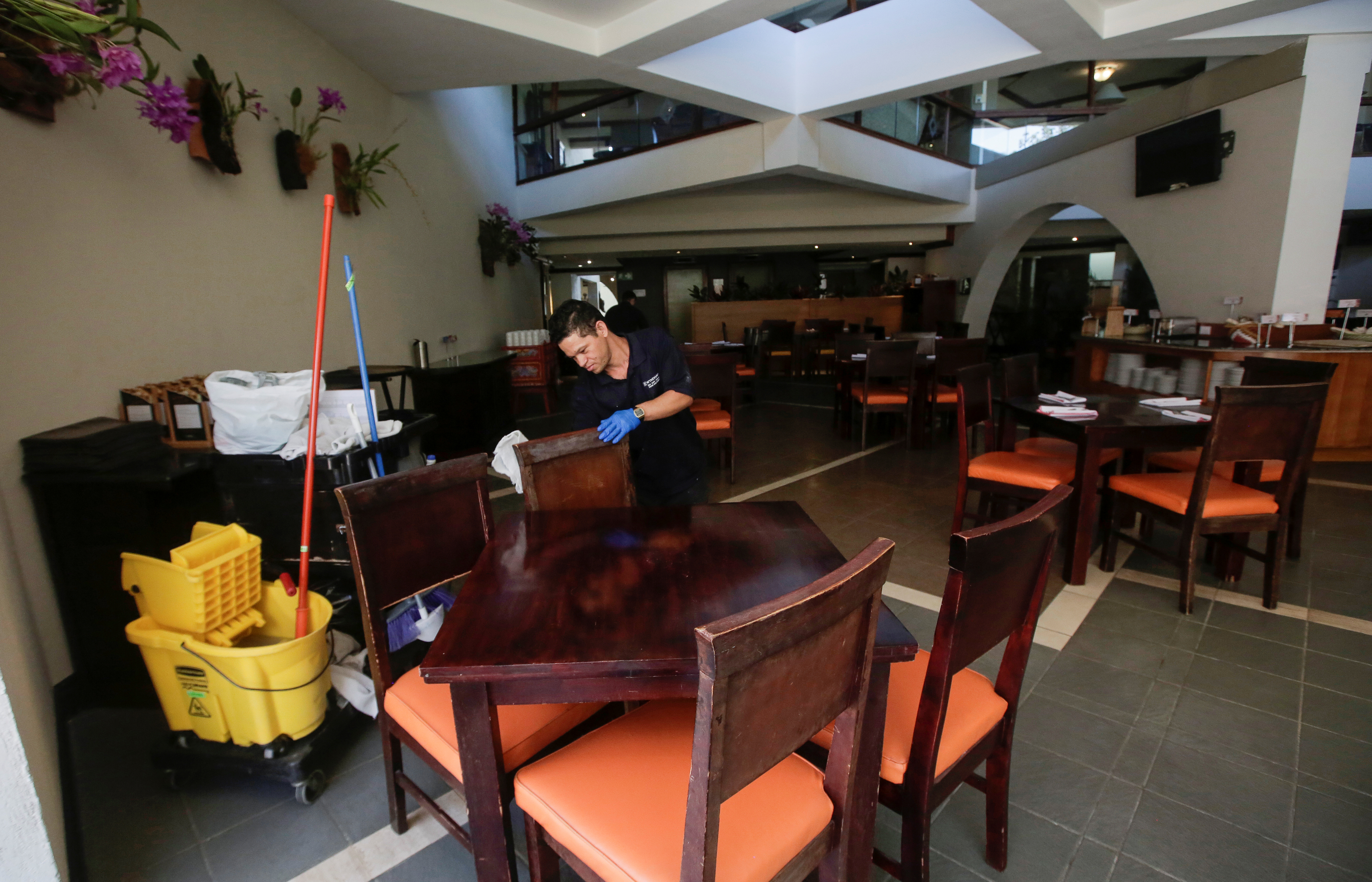 An employee cleans a restaurant chair in a hotel, as Costa Rica tourism industry braces for coronavirus disease (COVID-19) outbreak, in Heredia, Costa Rica March 18, 2020. Picture taken March 18,2020. REUTERS/Juan Carlos Ulate
