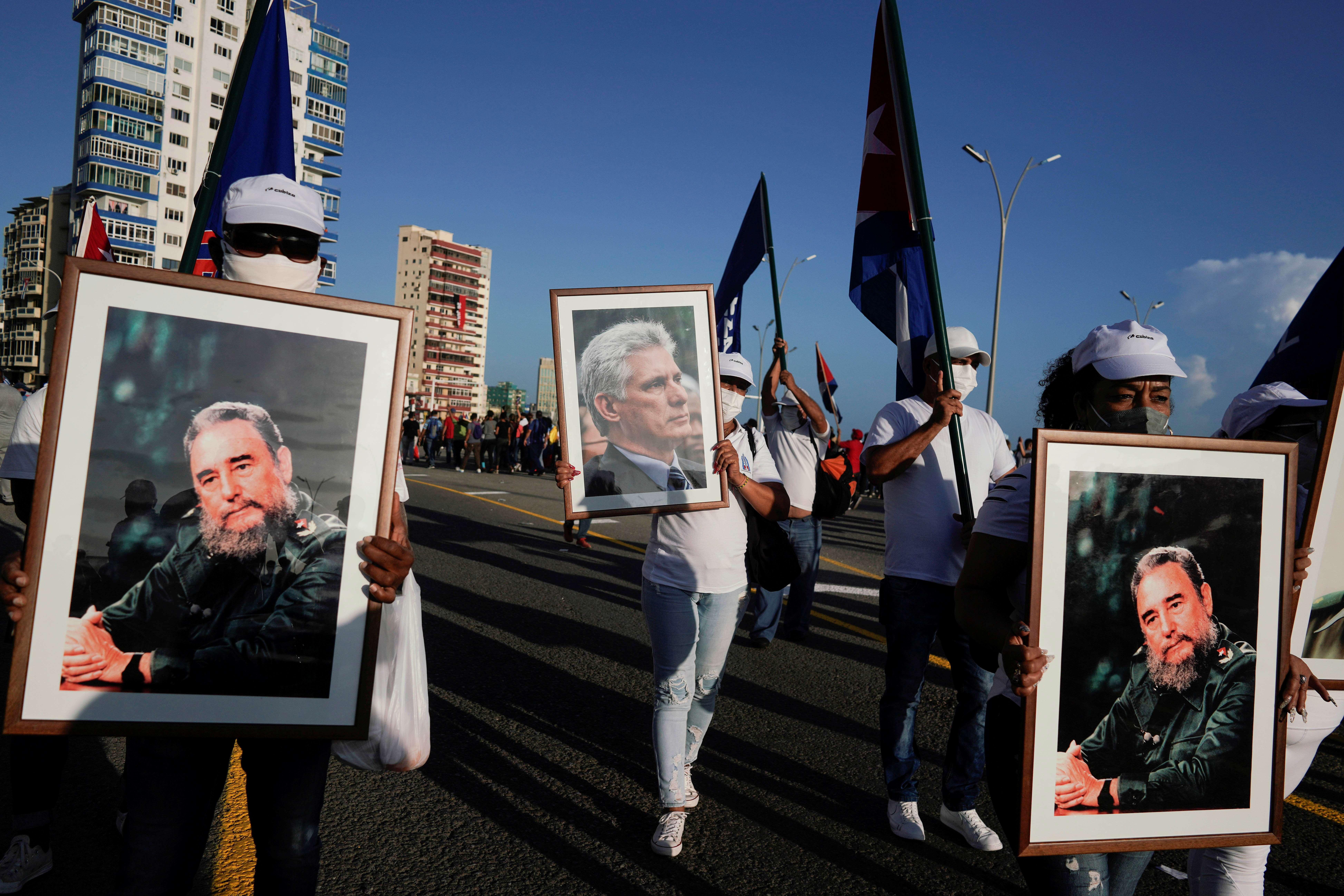People carry images of late Cuban President Fidel Castro and Cuba's President and First Secretary of the Communist Party Miguel Diaz-Canel during a rally in Havana, Cuba, July 17, 2021. REUTERS/Alexandre Meneghini