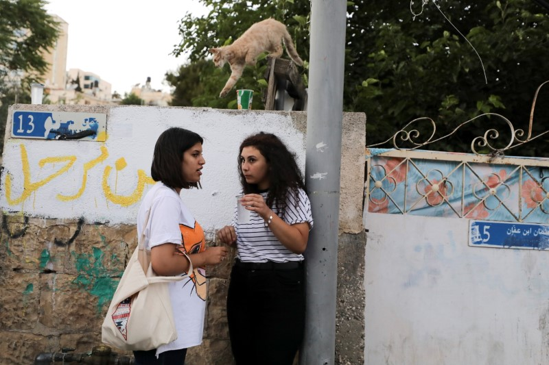 Tala, a member of the Abu Diab family, Palestinian residents of Sheikh Jarrah who face possible eviction after an Israeli court accepted Jewish settler land claims, speaks to a friend in her neighbourhood in East Jerusalem June 14, 2021 REUTERS/Ammar Awad