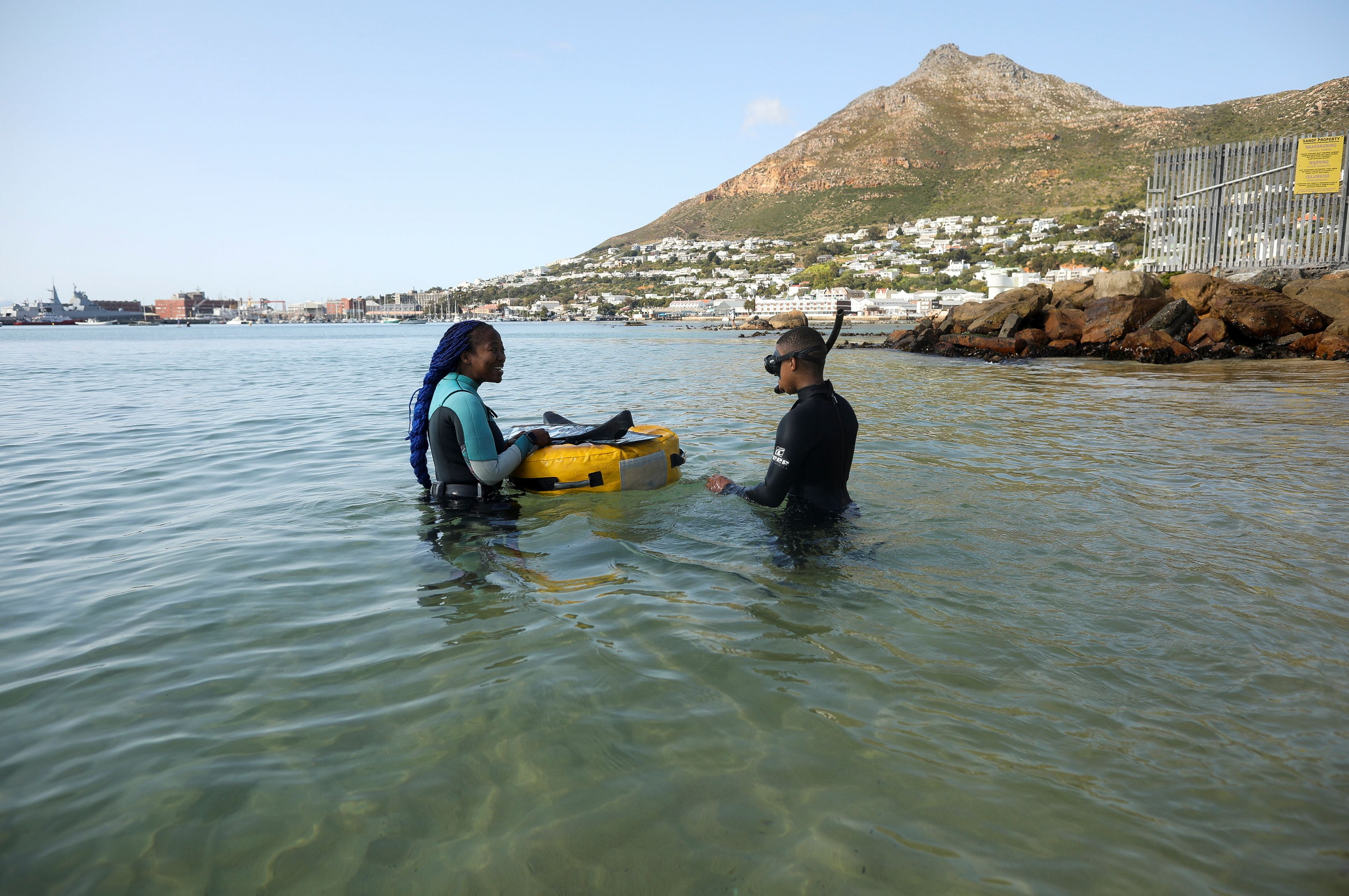 Free diver Zandile Ndlovu encourages a township youth to explore the marine world off Simonstown, near Cape Town, South Africa, August 22, 2021. Picture taken August 22, 2021. REUTERS/Mike Hutchings
