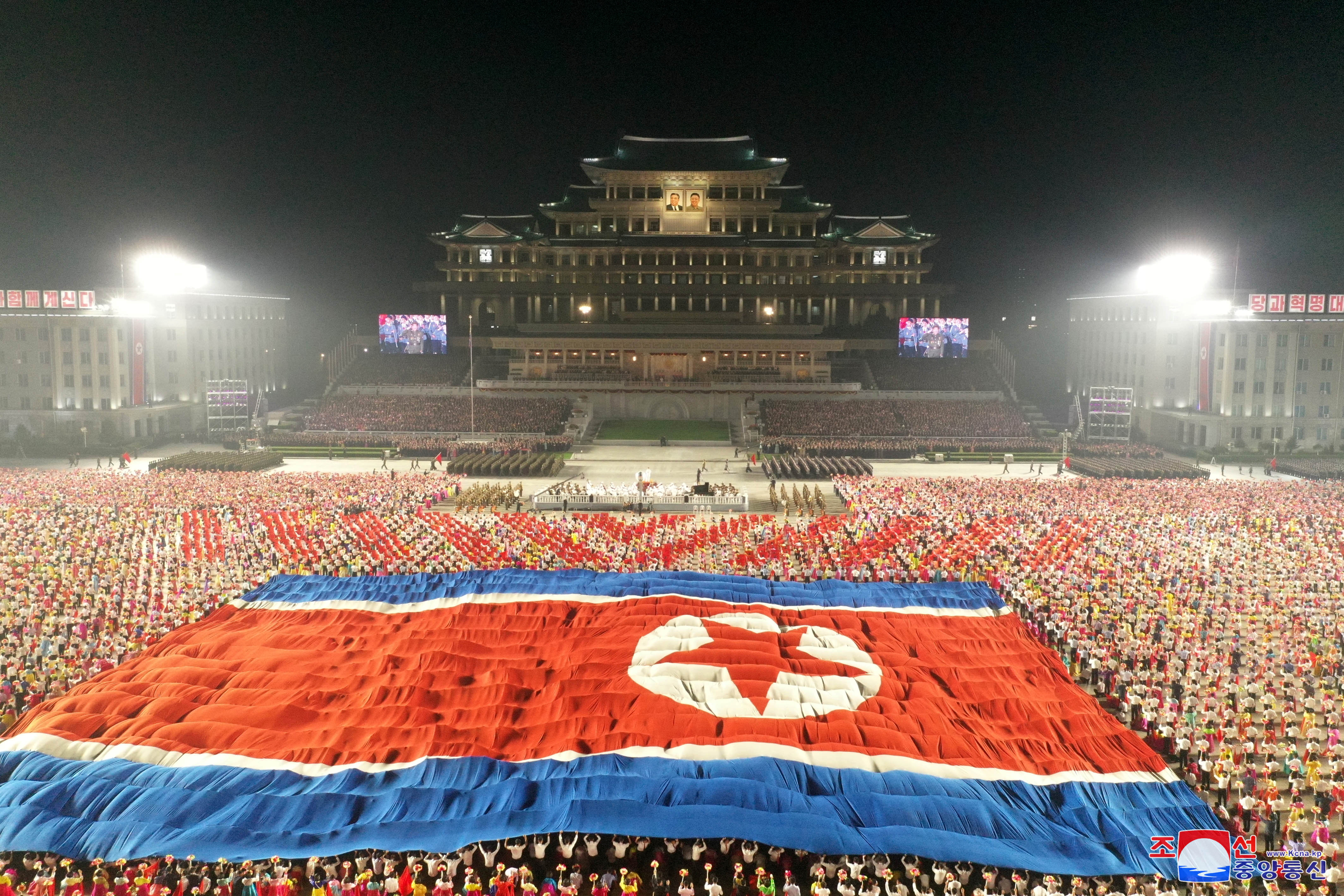 A giant North Korean flag is unhurled during a paramilitary parade held to mark the 73rd founding anniversary of the republic at Kim Il Sung square in Pyongyang in this undated image supplied by North Korea's Korean Central News Agency on September 9, 2021. KCNA via REUTERS