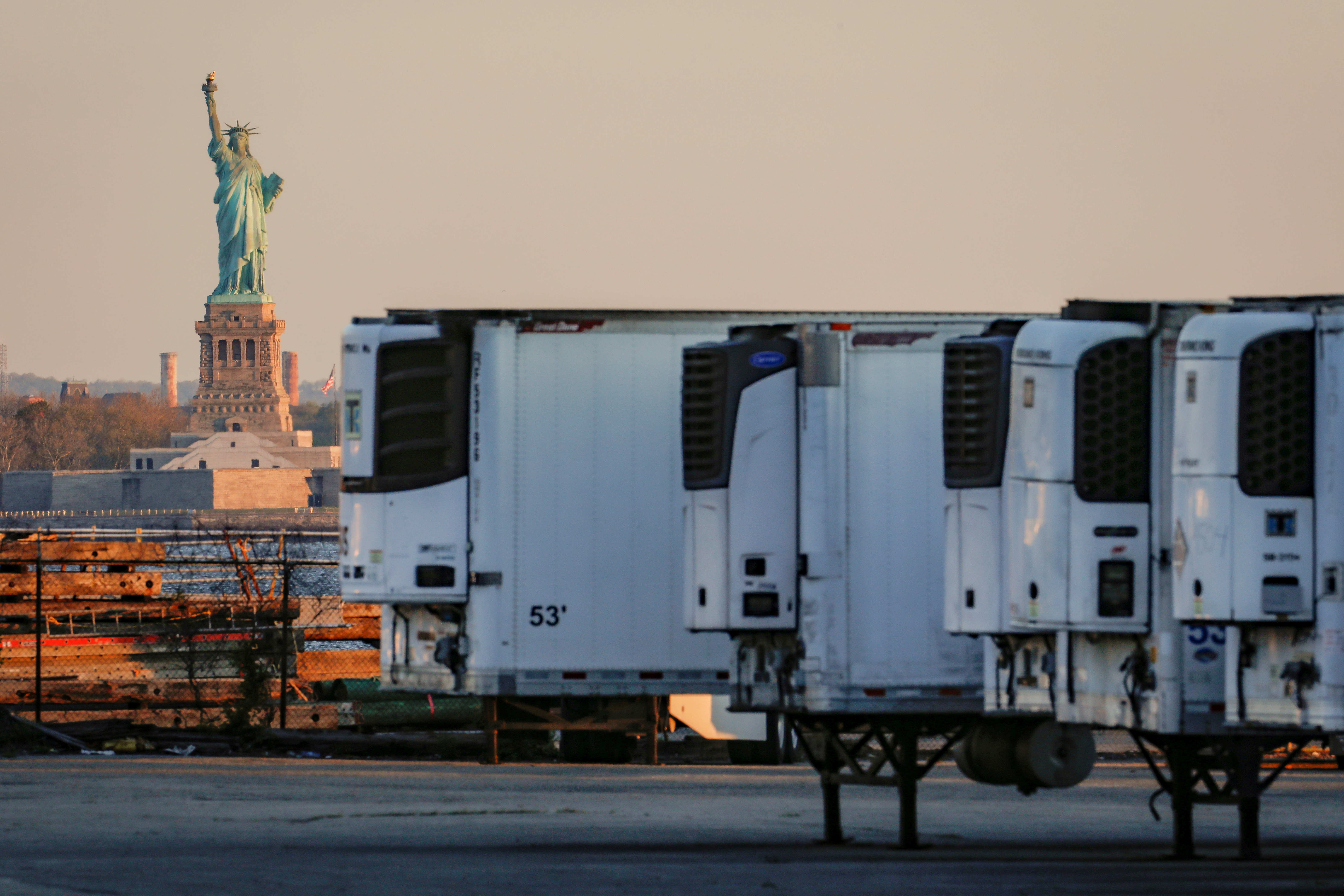 Refrigerated tractor trailers used to store bodies of deceased people are seen at a temporary morgue, with the Statue of Liberty seen in the background, during the coronavirus disease (COVID-19) outbreak, in the Brooklyn borough of New York City, U.S., May 13, 2020. REUTERS/Brendan McDermid/File Photo