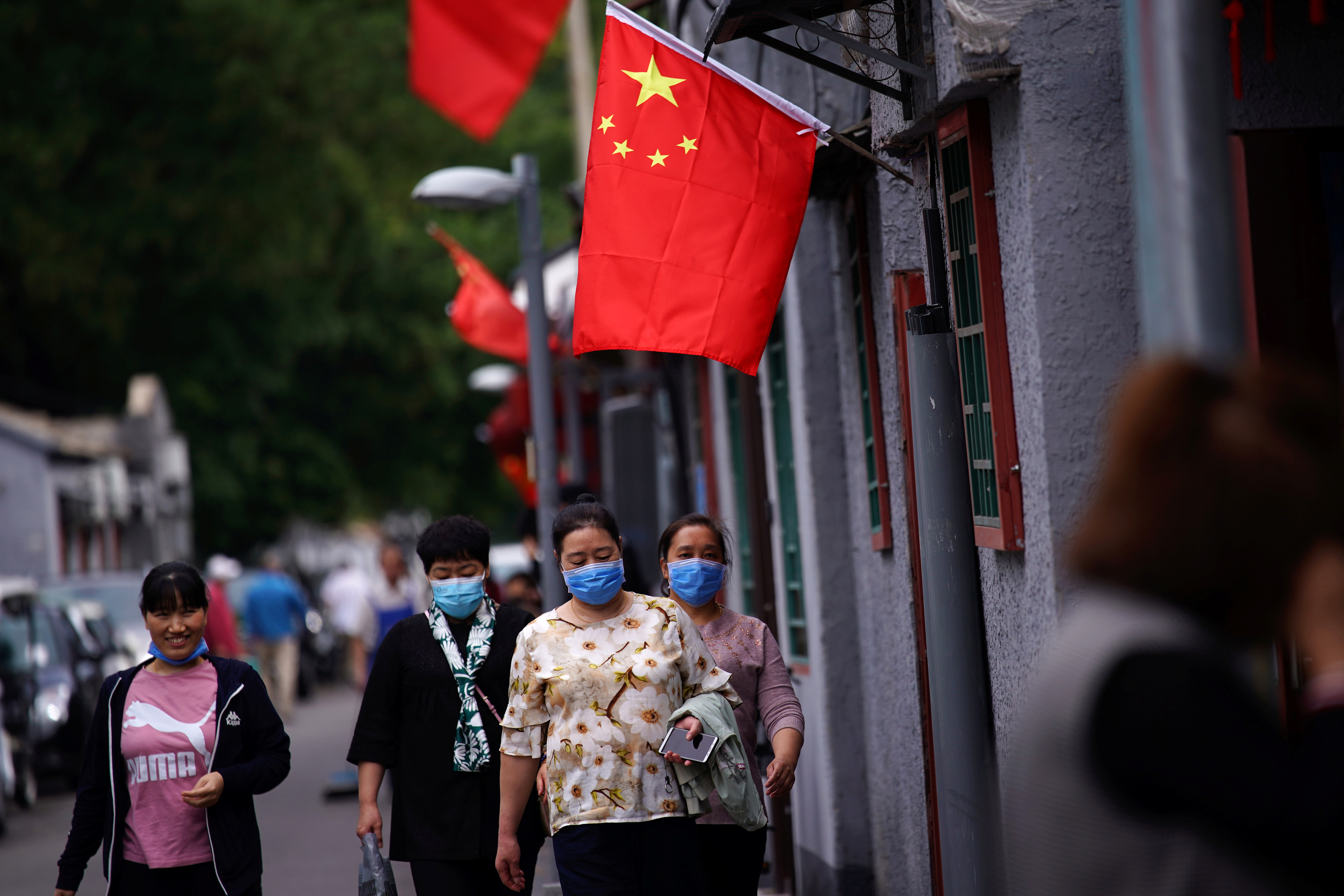 People wearing face masks following the coronavirus disease (COVID-19) outbreak walk at a hutong alley with Chinese national flags hung aside ahead of the Chinese National Day on October 1, in Beijing, China September 29, 2020. REUTERS/Tingshu Wang/Files