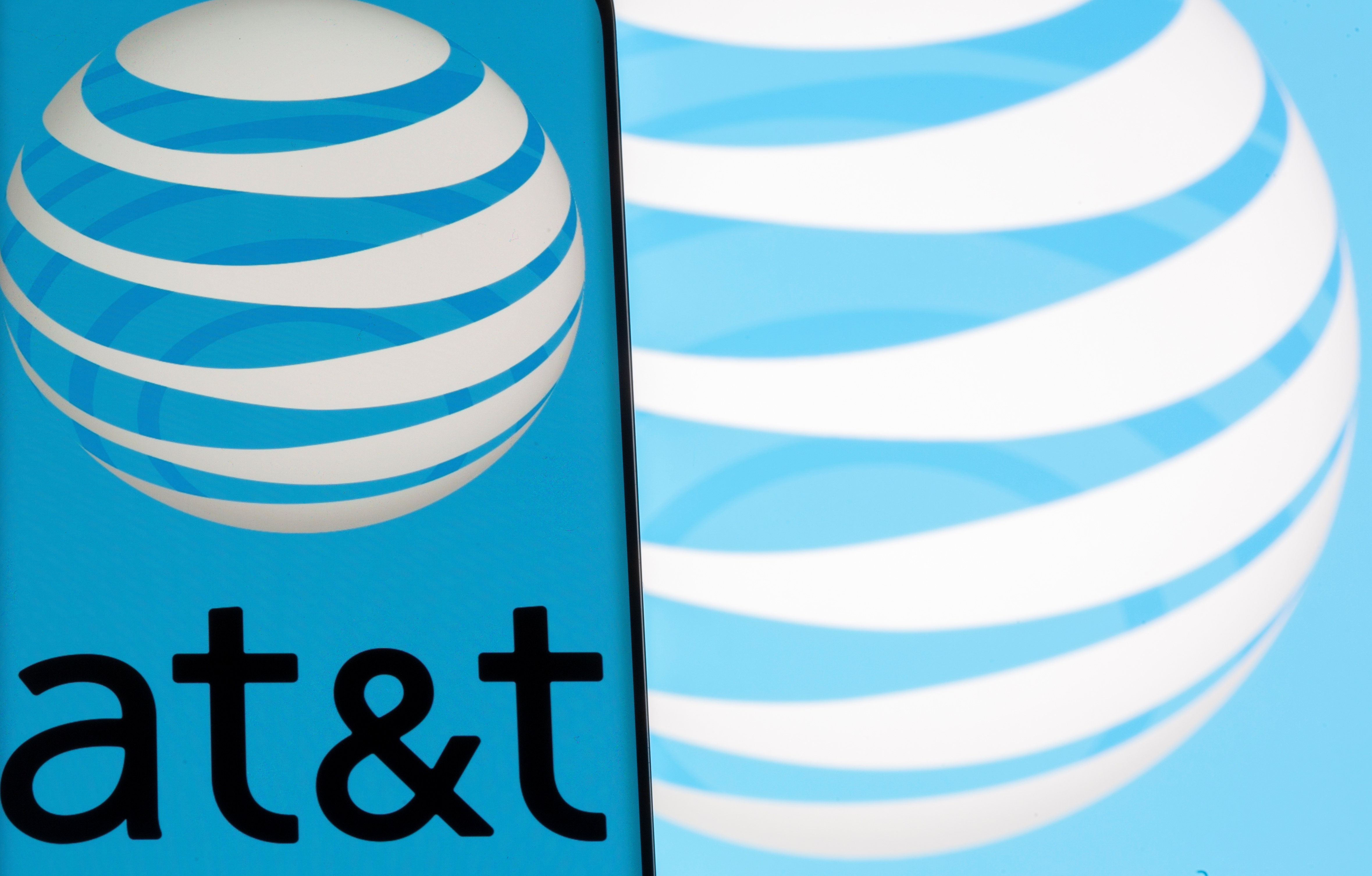 AT&T logo is seen on a smartphone in front of displayed same logo in this illustration taken May 17, 2021. REUTERS/Dado Ruvic