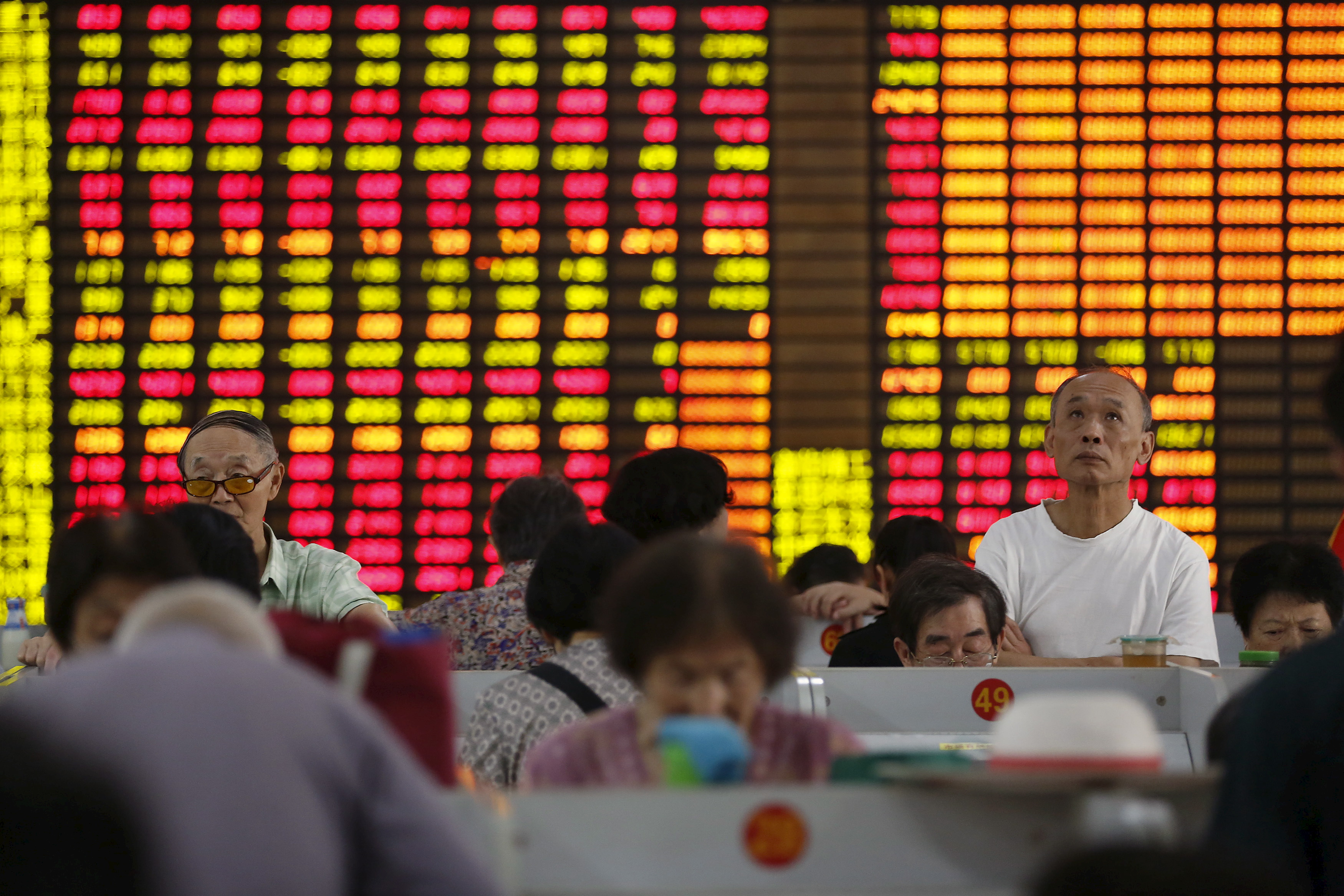 Investors look at computer screens showing stock information at a brokerage in Shanghai, China, August 13, 2015. REUTERS/Aly Song