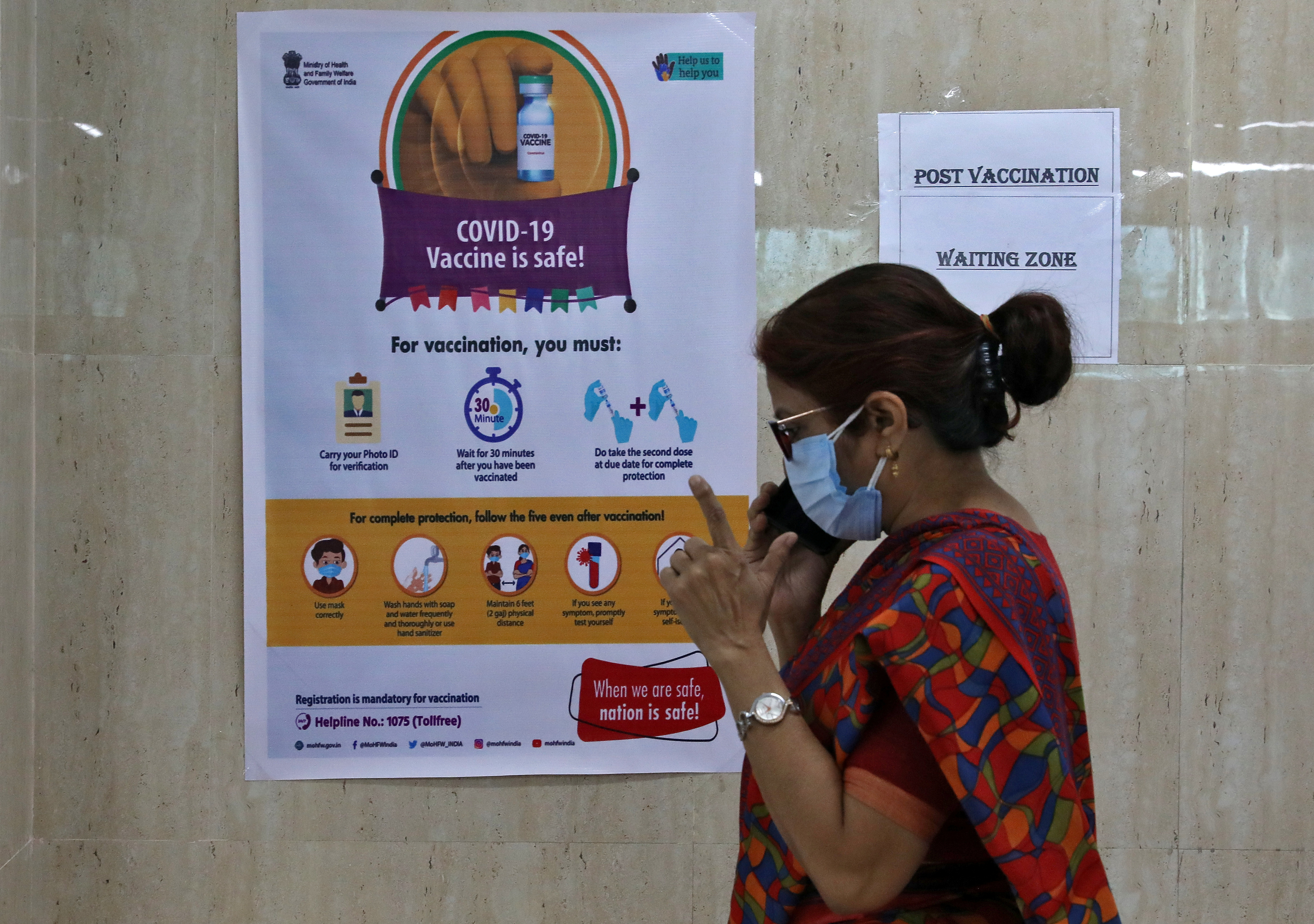 A woman speaks inside a waiting zone area at a health clinic where COVID-19 vaccination is being given to healthcare workers in Kolkata, India, February 1, 2021. REUTERS/Rupak De Chowdhuri