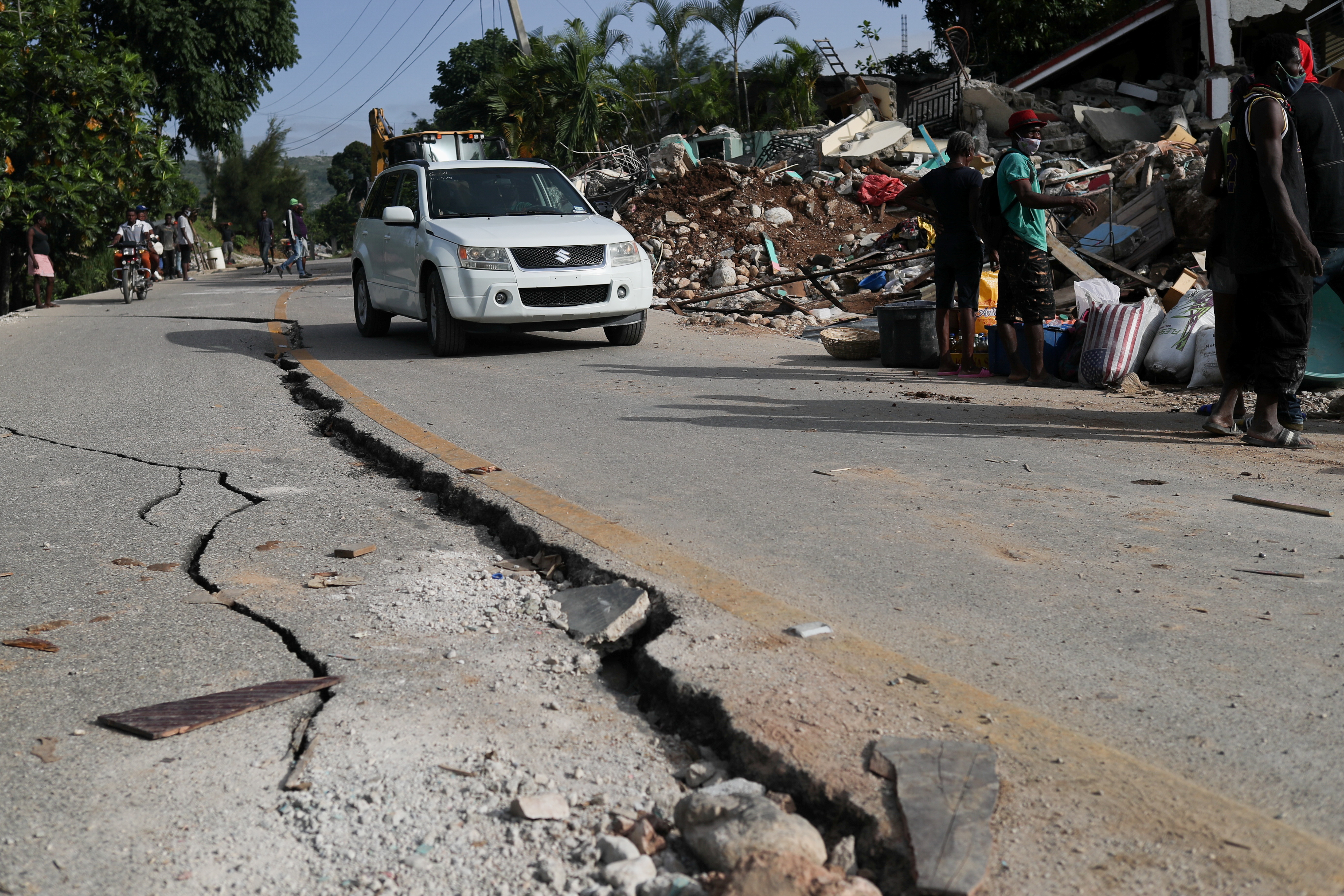 A car drives past a damaged road, after the earthquake that took place on August 14th, in Marceline, near Les Cayes, Haiti August 20, 2021. REUTERS/Henry Romero