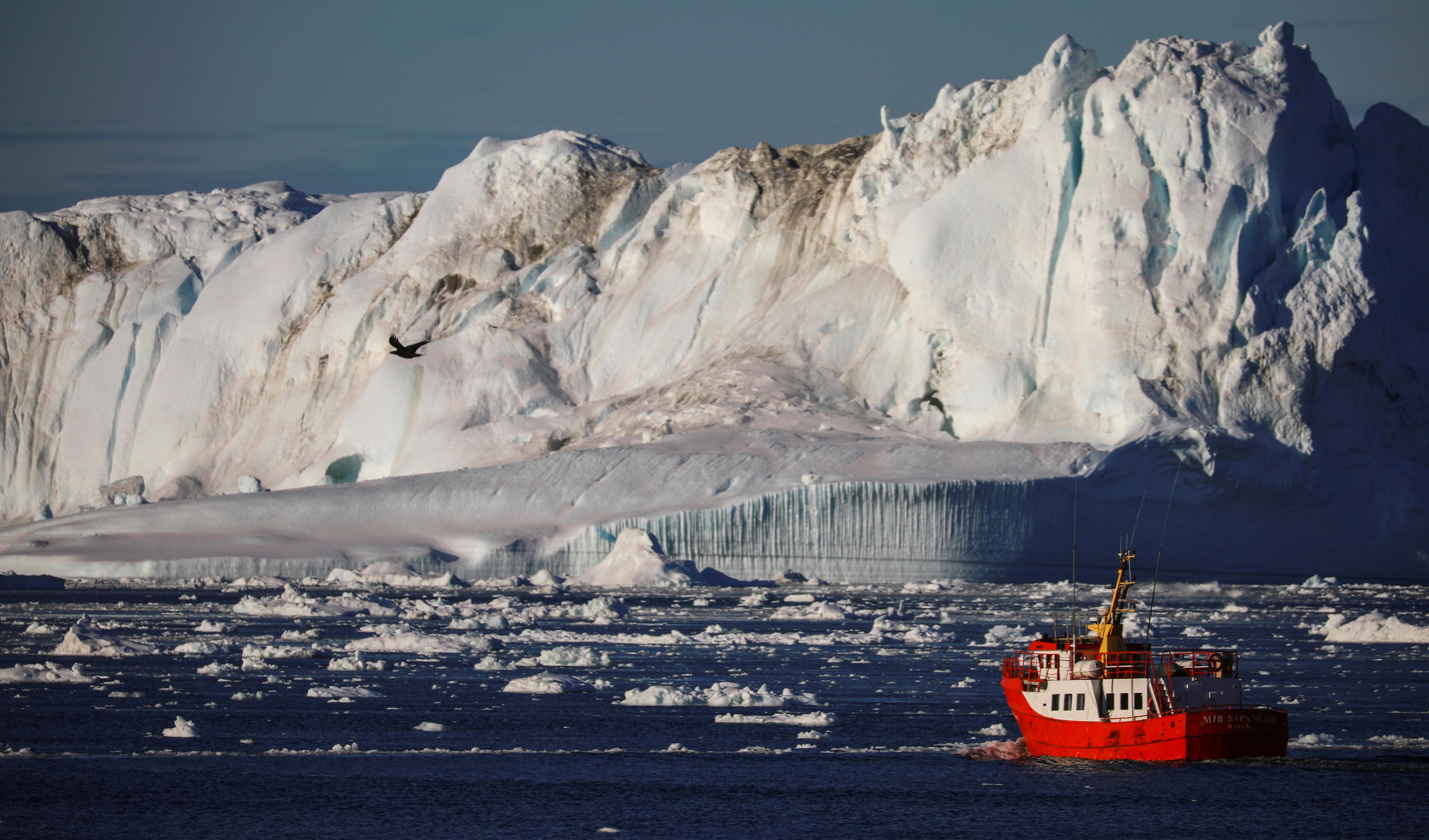 A boat passes icebergs at the Disko Bay near Ilulissat, Greenland, September 16. REUTERS/Hannibal Hanschke/File Photo