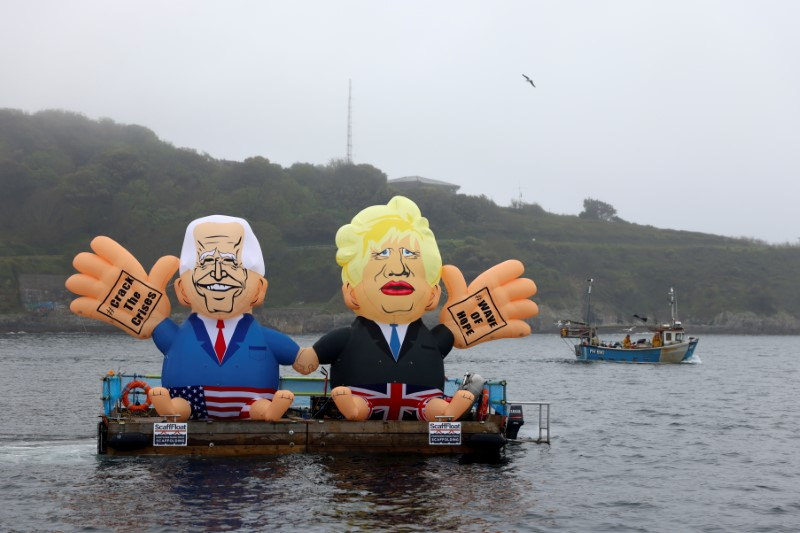 Inflatable dummies depicting U.S. President Joe Biden and Britain's Prime Minister Boris Johnson are displayed on a pontoon floating off Gyllyngvase Beach during an action organized by Crack the Crisis, in Falmouth, on the sidelines of G7 summit in Cornwall, Britain, June 11, 2021. REUTERS/Tom Nicholson