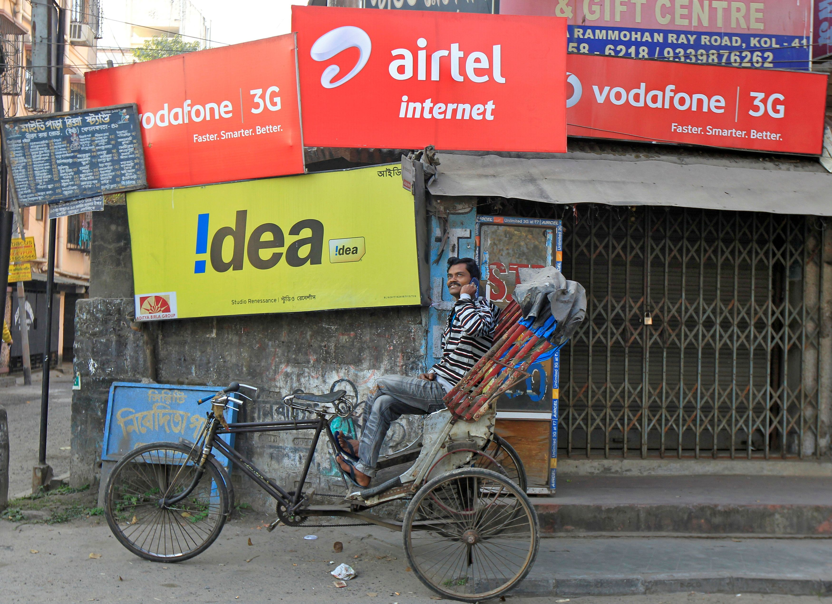 A rickshaw puller speaks on his mobile phone as he waits for customers in front of advertisement billboards belonging to telecom companies in Kolkata, India, February 3, 2014.  REUTERS/Rupak De Chowdhuri/File Photo