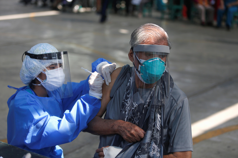 A senior citizen receives a dose of the Pfizer-BioNTech coronavirus disease (COVID-19) vaccine in Lima, Peru March 23, 2021. REUTERS/Sebastian Castaneda
