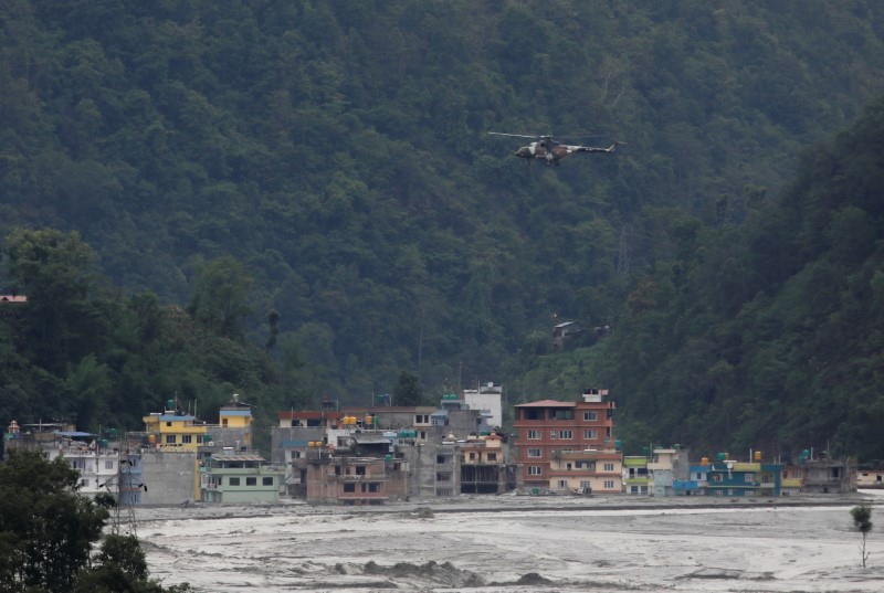 A helicopter belonging to Nepal army flies past houses hit by flash floods along the bank of Melamchi River during a rescue mission in Sindhupalchok, Nepal June 16, 2021. REUTERS/Navesh Chitrakar