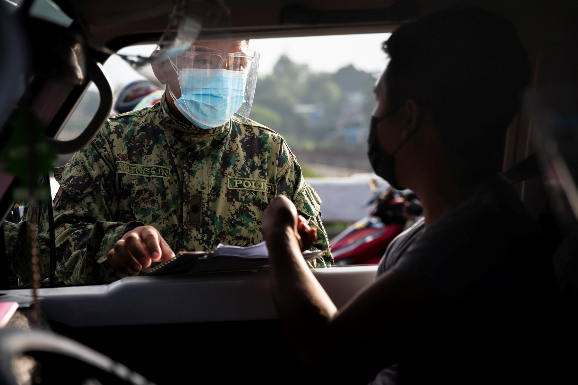 A policeman inspects the papers of a passenger passing through a checkpoint on the first day of a two-week lockdown to prevent the spread of the highly infectious coronavirus Delta variant, in Quezon City, Metro Manila, Philippines, August 6, 2021. REUTERS/Eloisa Lopez