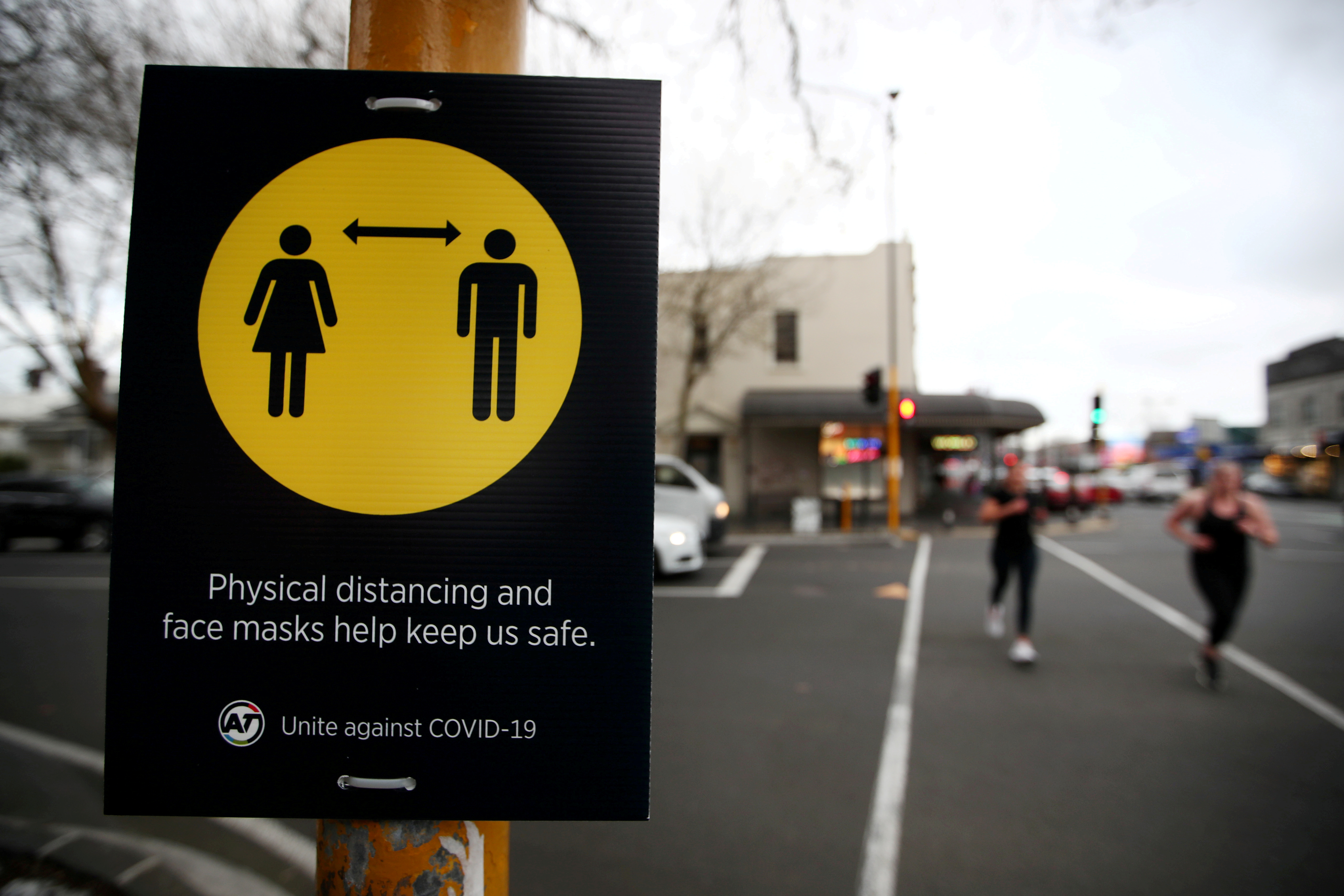 People jog past a social distancing sign on the first day of New Zealand's new coronavirus disease (COVID-19) safety measure that mandates wearing of a mask on public transport, in Auckland, New Zealand, August 31, 2020.  REUTERS/Fiona Goodall/File Photo