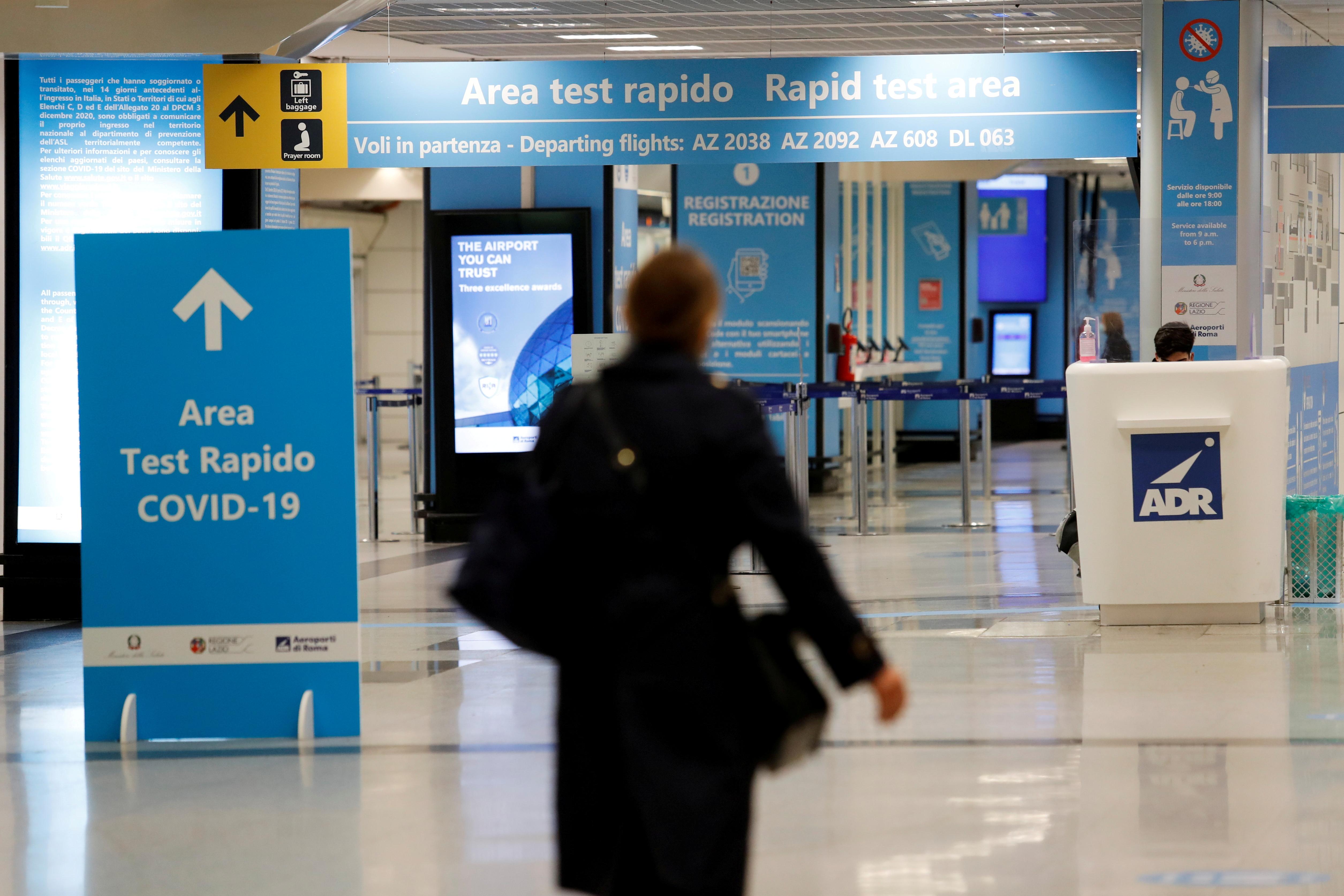 A person walks near a COVID-19 test area at Fiumicino airport in Rome, Italy, December 24, 2020. REUTERS/Remo Casilli/File Photo