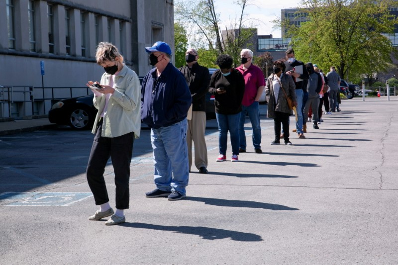 FILE PHOTO: People line up outside a newly reopened career center for in-person appointments in Louisville, U.S., April 15, 2021.  REUTERS/Amira Karaoud/File Photo