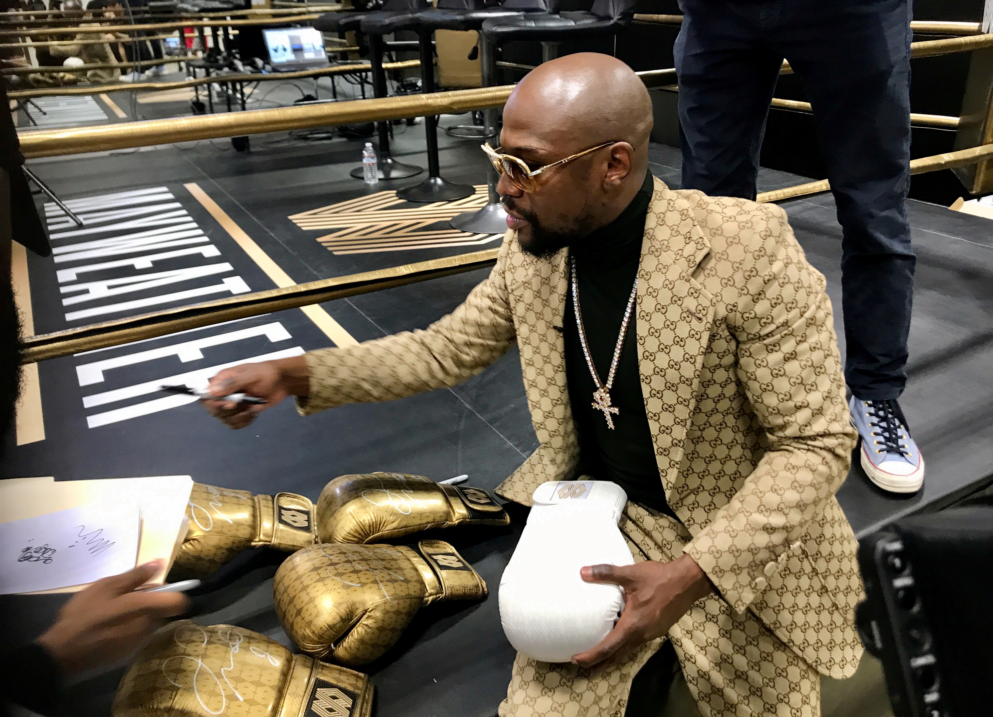 Floyd Mayweather signs gloves at the opening of the Mayweather Boxing + Fitness gym in Torrance, California, U.S., November 16, 2019.  REUTERS/Rory Carroll/File Photo
