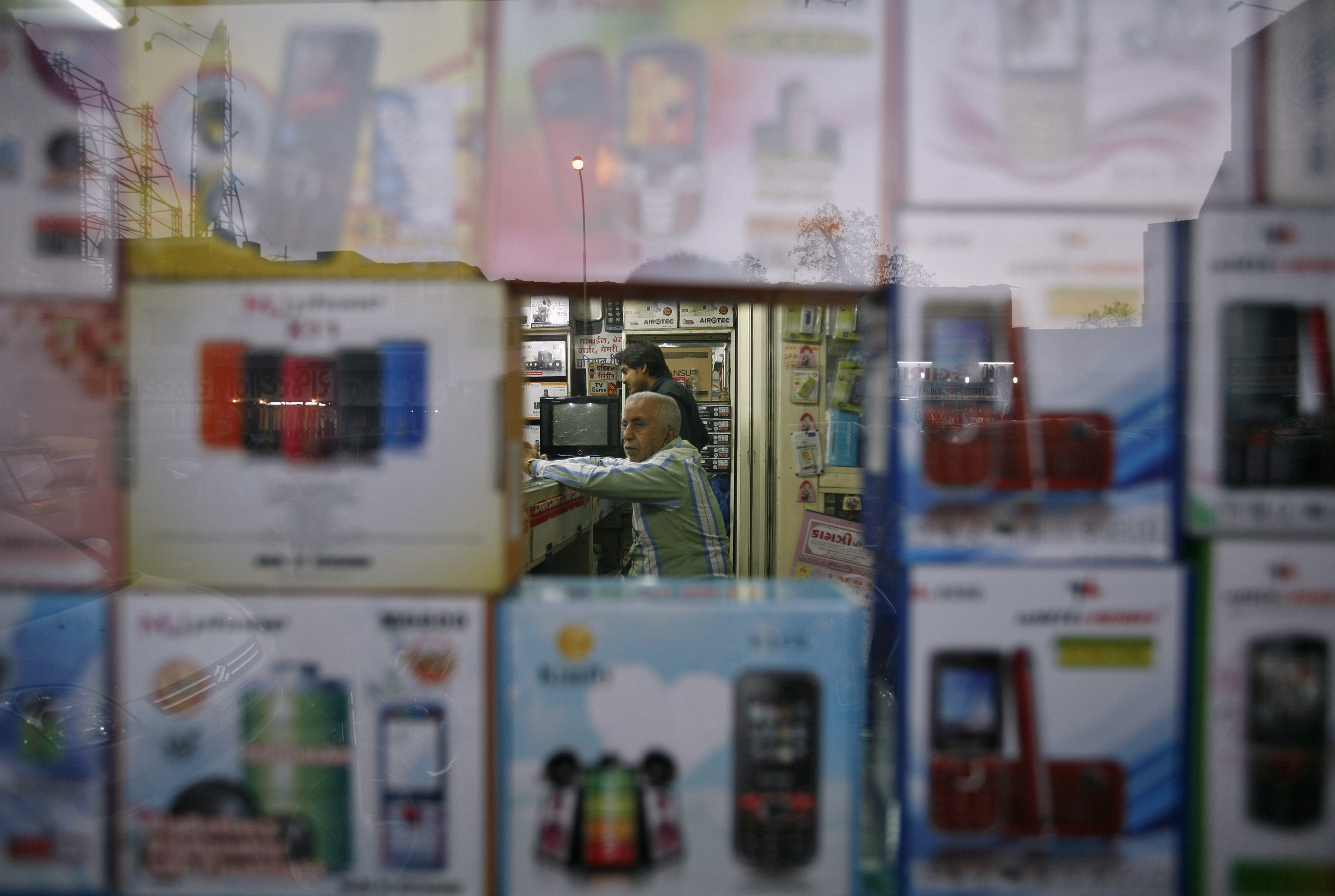 A vendor waits for customers inside his shop that sells mobile phones at Surat, in the western Indian state of Gujarat January 4, 2013. REUTERS/Amit Dave
