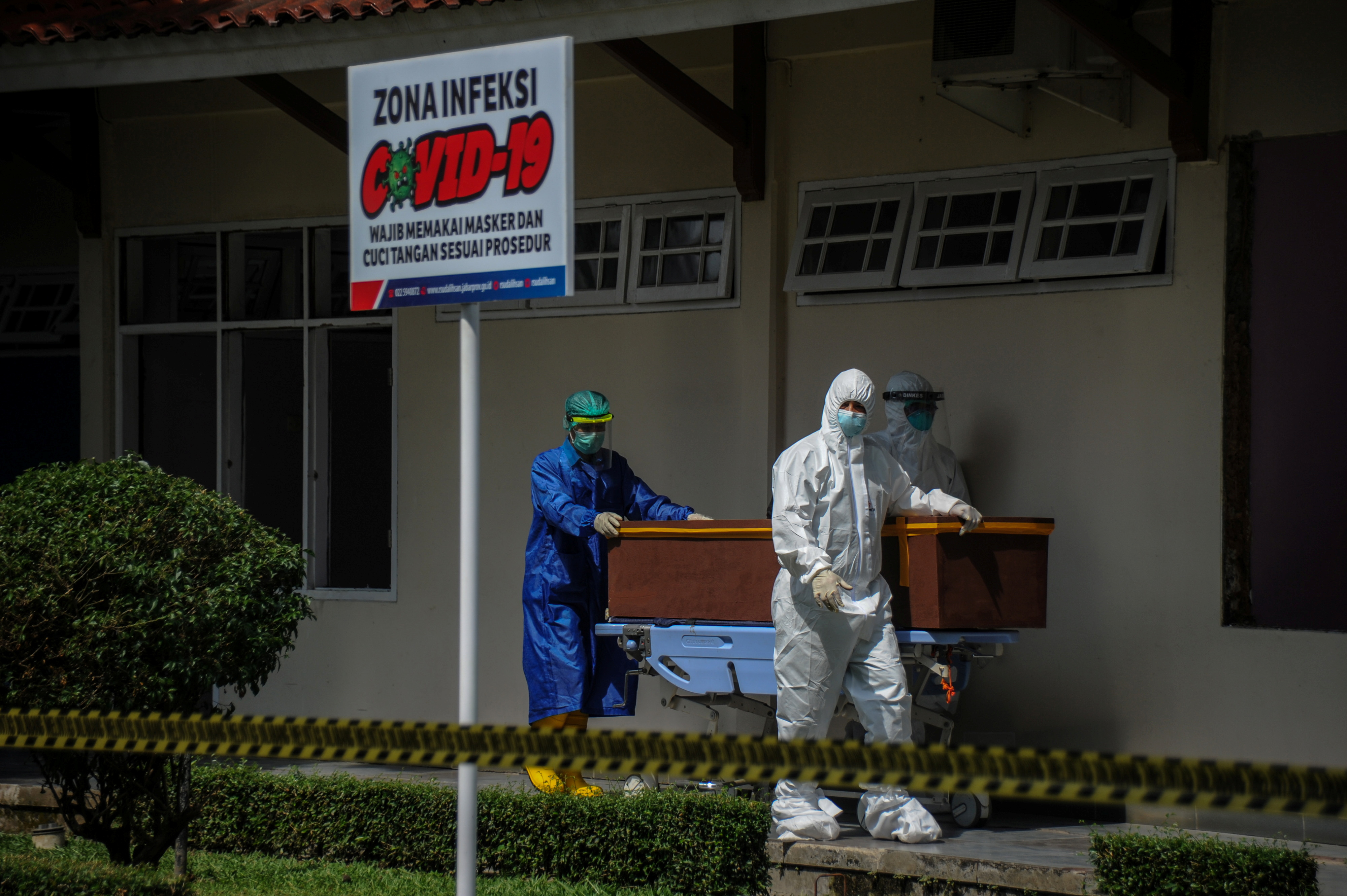 Healthcare workers wearing PPE (personal protective equipment) carry the coffin of a victim of the coronavirus disease (COVID-19) at a hospital in Bandung, West Java Province, Indonesia June 17, 2021, in this photo taken by Antara Foto/Raisan Al Farisi/via Reuters.