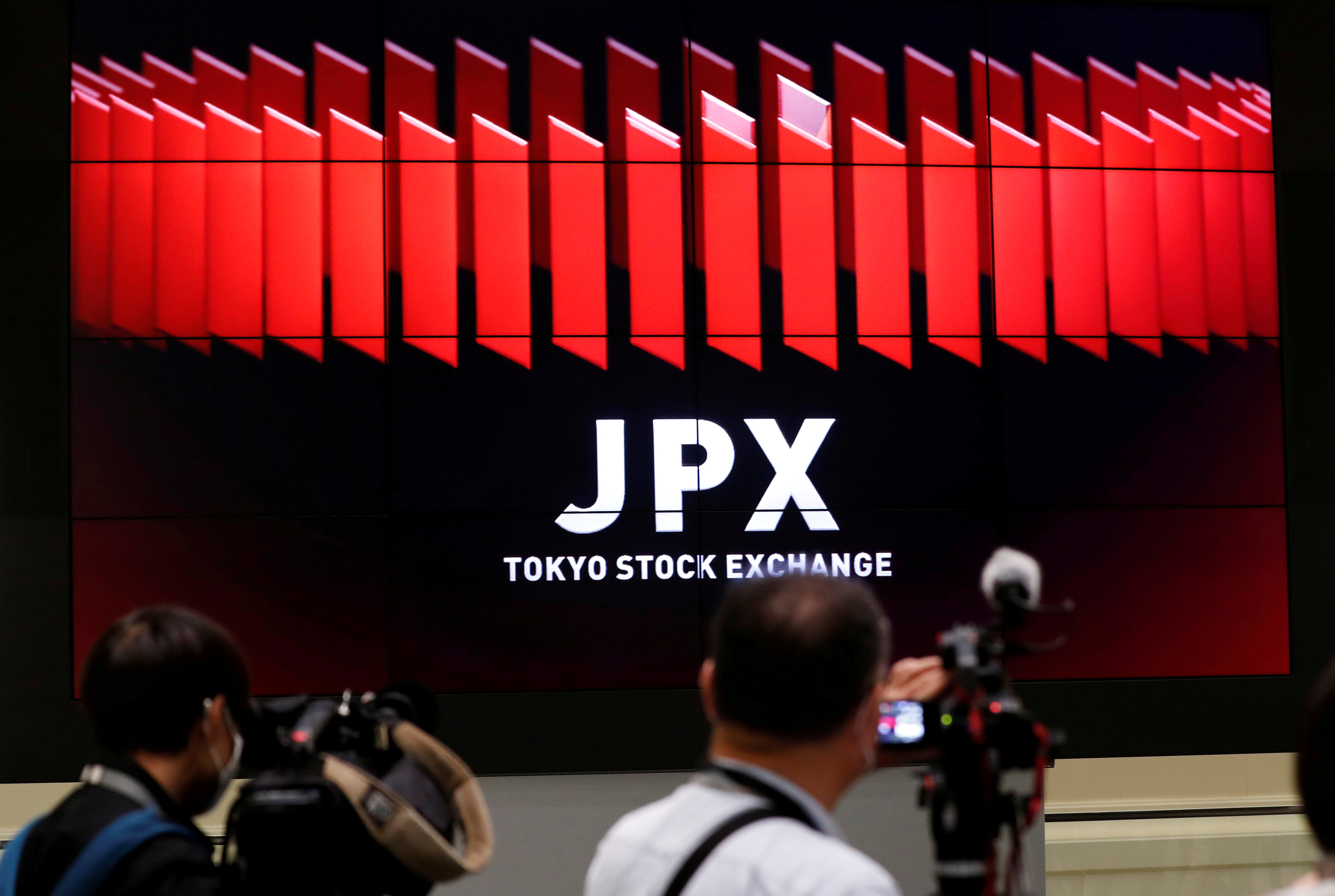 TV camera men wait for the opening of market in front of a large screen showing stock prices at the Tokyo Stock Exchange in Tokyo, Japan October 2, 2020. REUTERS/Kim Kyung-Hoon/File Photo