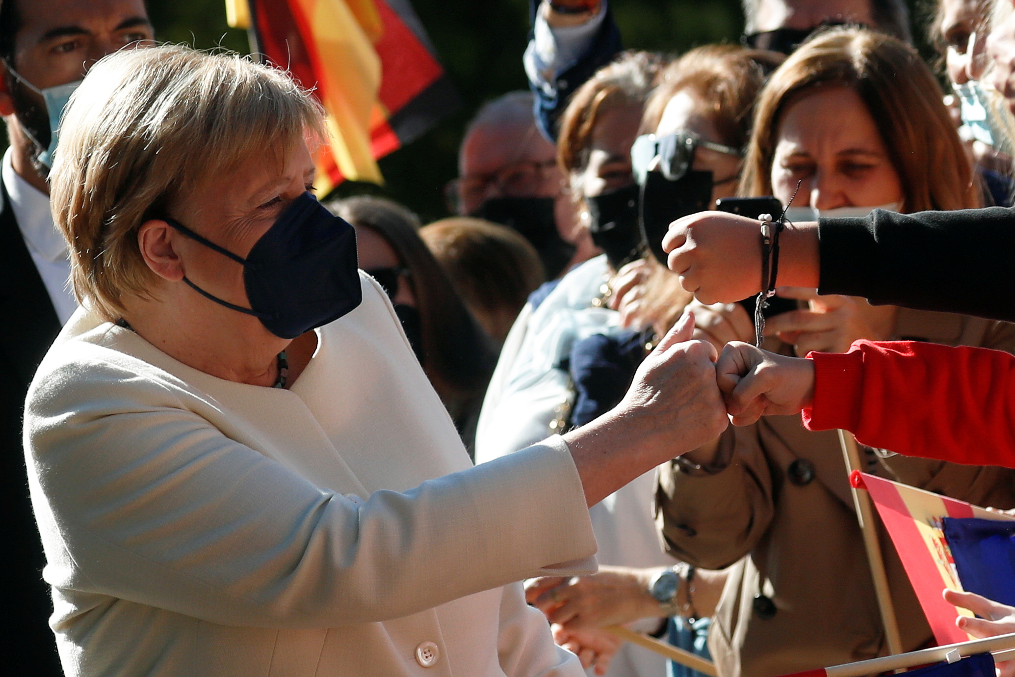 German Chancellor Angela Merkel greets people upon her arrival to receive the