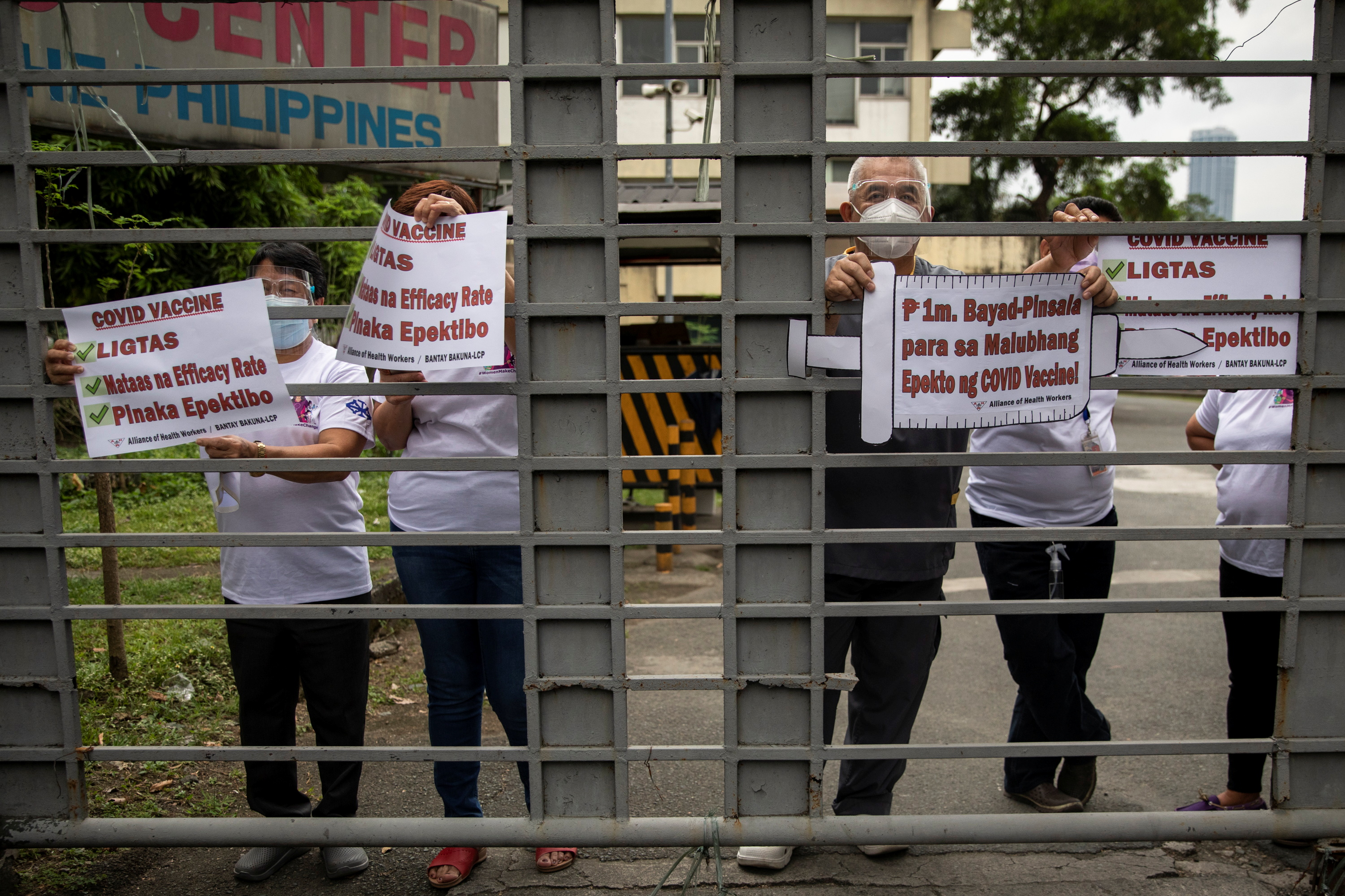 Hospital workers join a protest calling for free, safe, and most efficacious coronavirus disease (COVID-19) vaccines from the gates of the Lung Center of the Phillipines where the government kicked off its COVID-19 vaccination campaign with Sinovac Biotech's Coronavac vaccines, at Quezon City, Metro Manila, Philippines, March 1, 2021. REUTERS/Eloisa Lopez