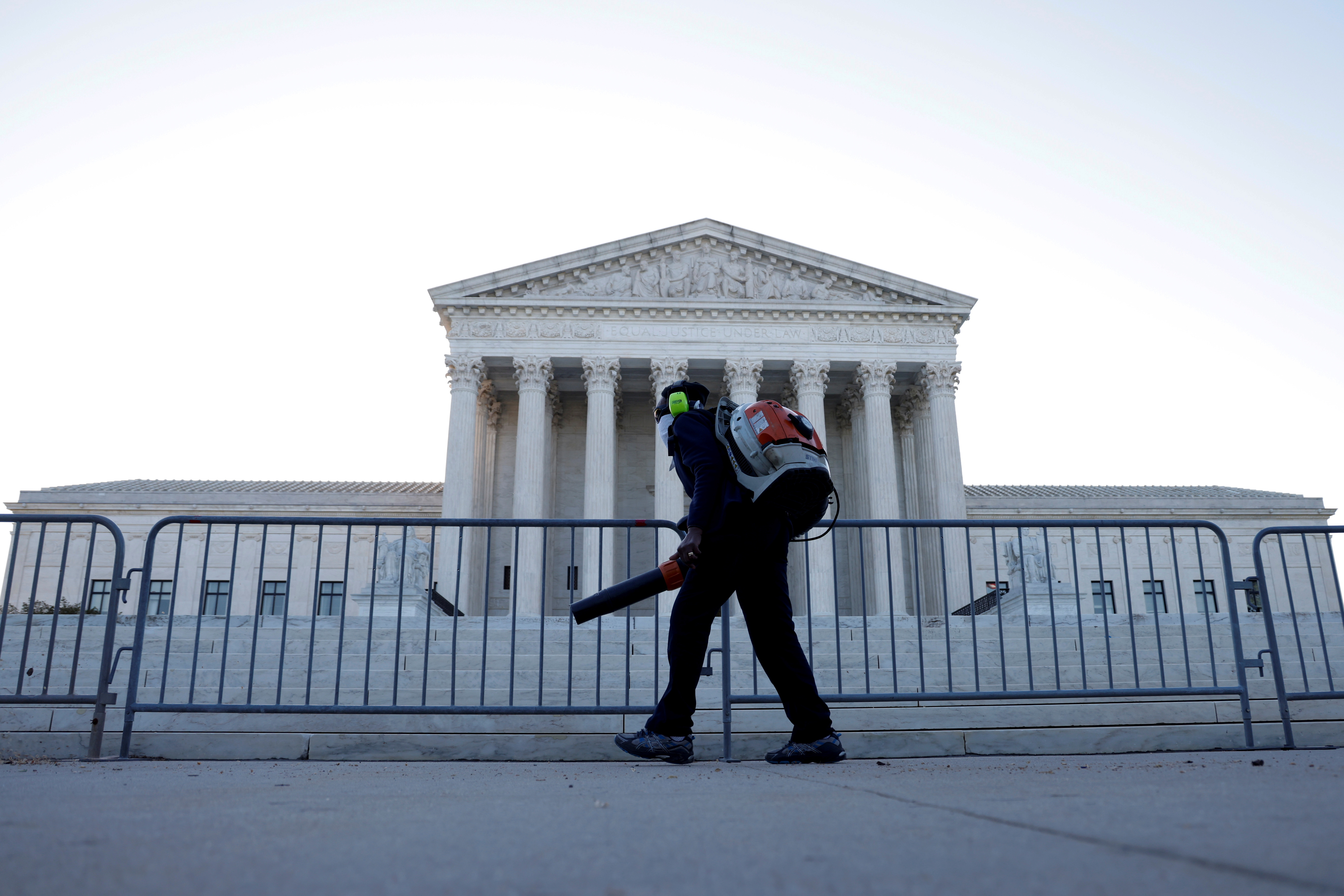A worker clears front steps as morning rises over the U.S. Supreme Court building, still closed to the public during the COVID-19 pandemic, in Washington, U.S. April 26, 2021.  REUTERS/Jonathan Ernst/File Photo