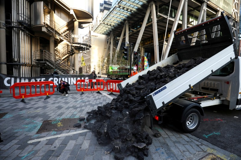 Activists from Extinction Rebellion, a global environmental movement, dump fake coal, made from rocks, into the street during a protest outside the Lloyd's building in London, Britain April 23, 2021. REUTERS/Henry Nicholls/File Photo