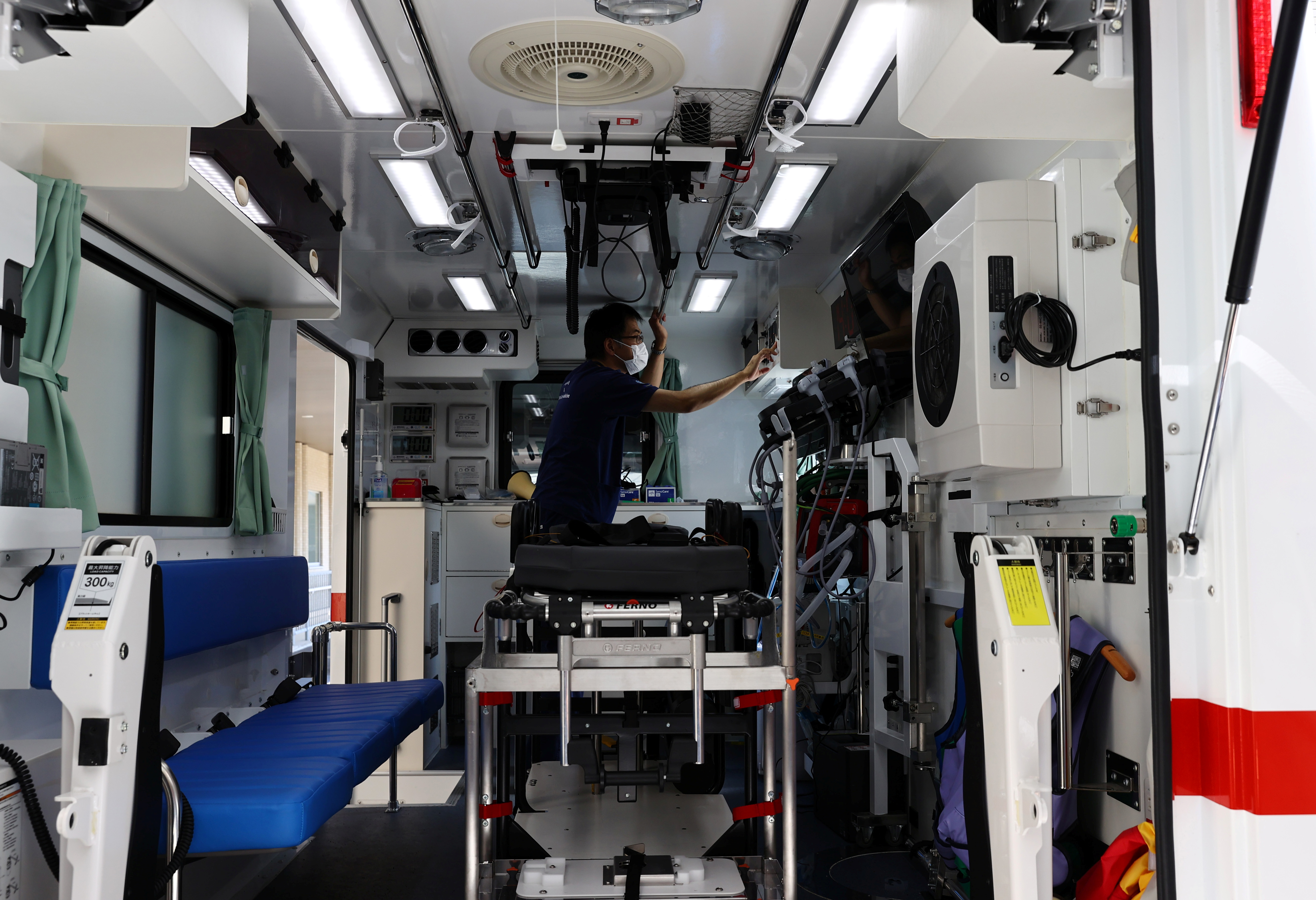 Nippon Medical School Hospital's ICU doctor Shoji Yokobori checks the devices of an ambulance, to prevent the spread of COVID-19 at the hospital in Tokyo, Japan, August 1, 2021. Picture taken on August 1, 2021.  REUTERS/Kim Kyung-Hoon/Files