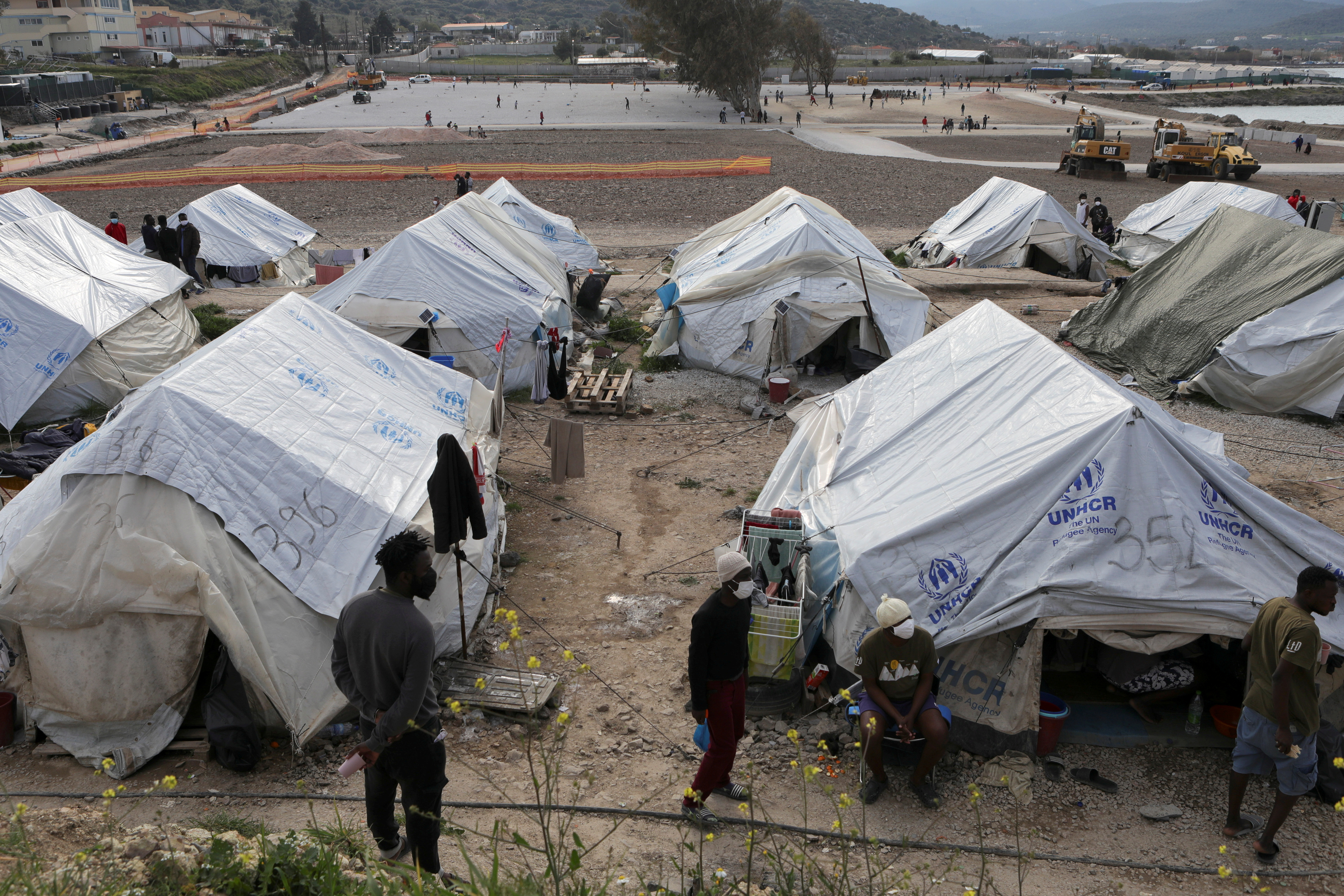 Refugees and migrants stand next to tents in the Mavrovouni camp on the island of Lesbos, Greece, March 29, 2021. REUTERS/Elias Marcou