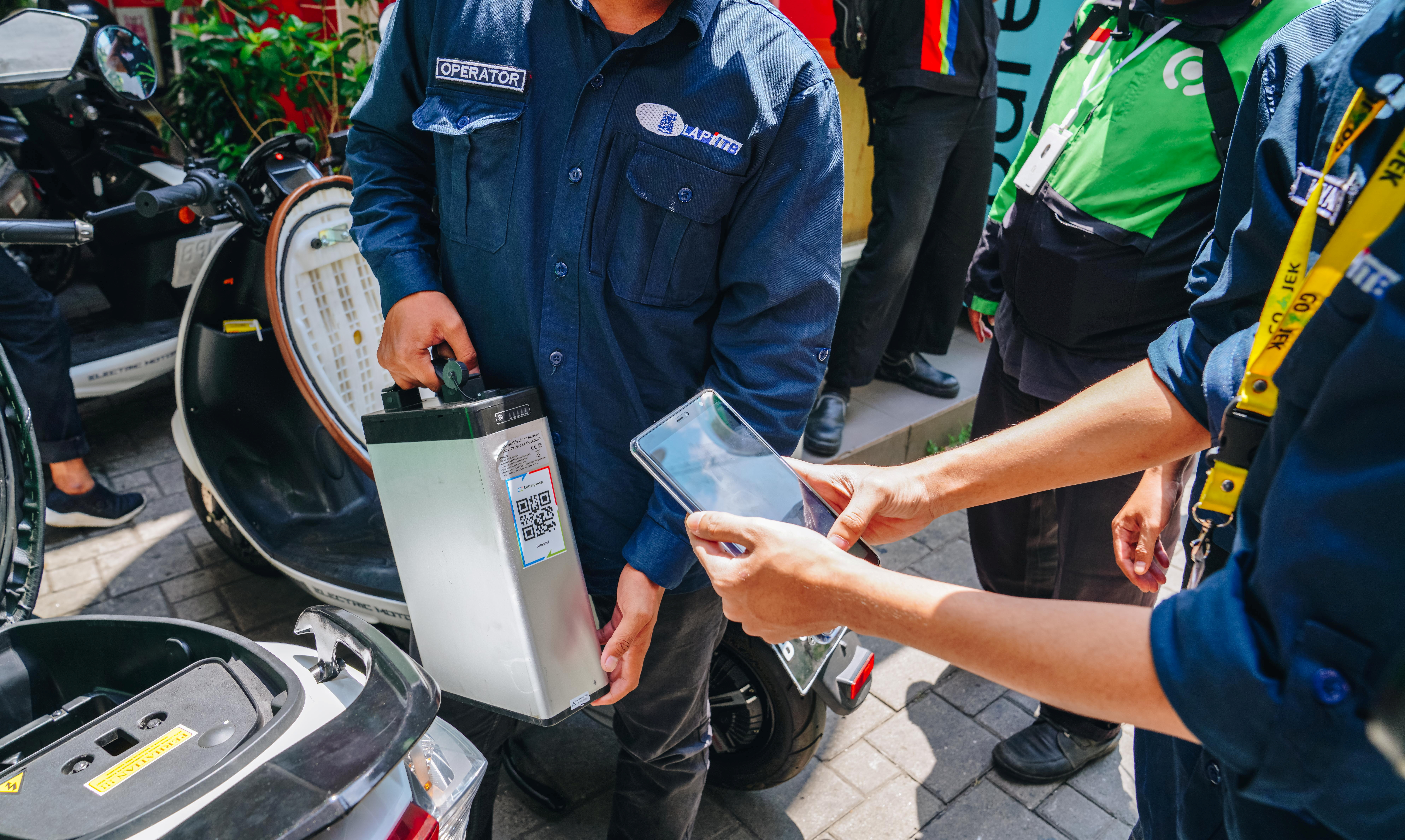 Operators scan a Gojek taxi rider's battery barcode to charge it at a charging station in Jakarta, Indonesia August 28, 2020. Picture taken August 28, 2020. Courtesy of GOJEK/Handout via REUTERS